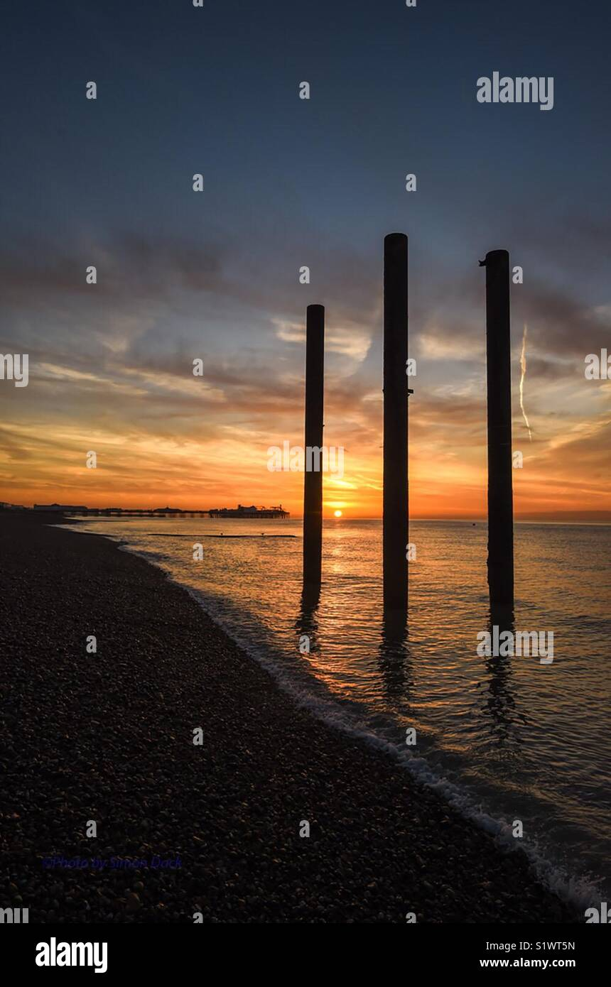 Sunrise on Brighton seafront by derelict West Pier pillars with Palace Pier in background - Stock Image