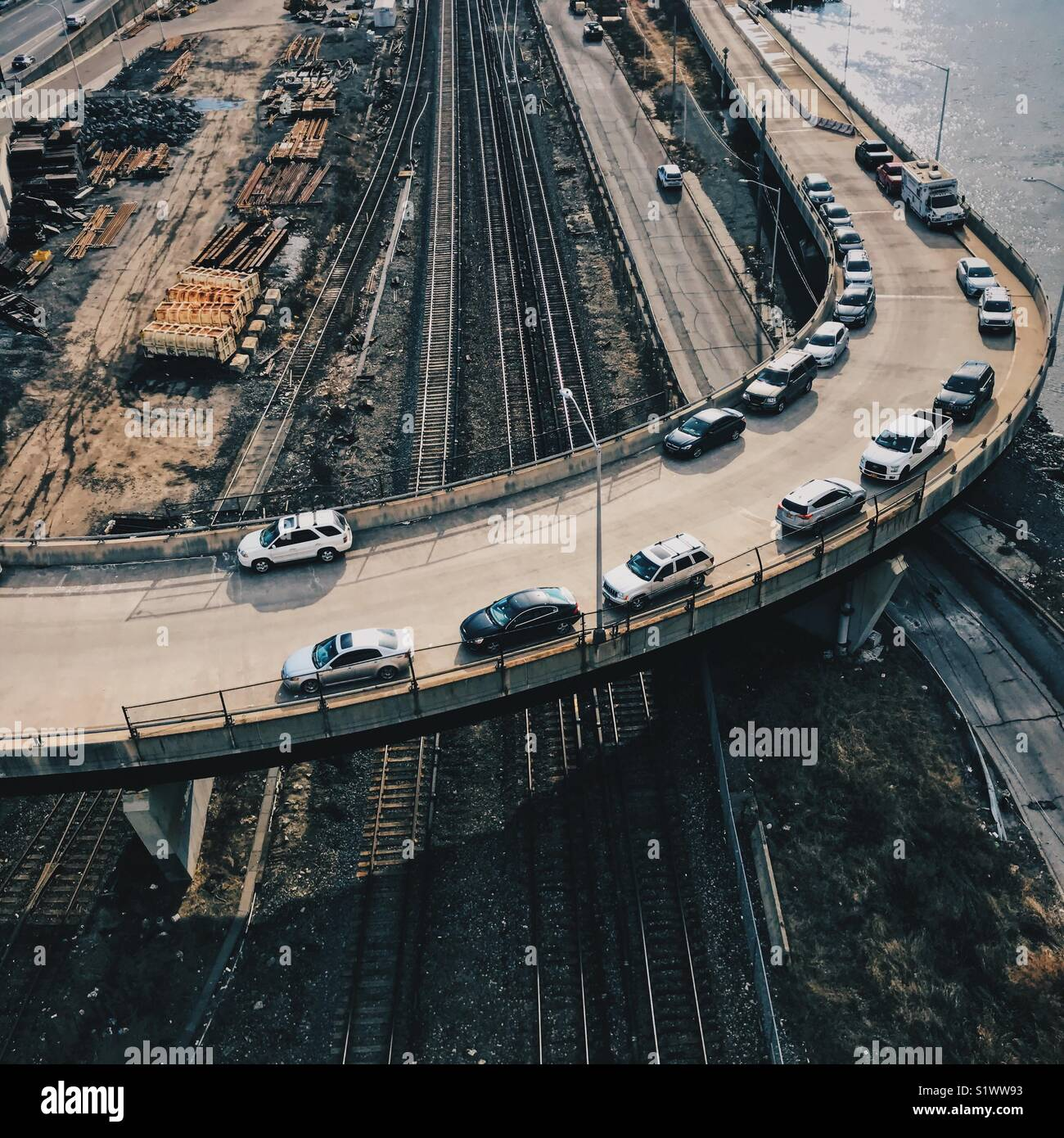 Cars parked on a curve over train tracks. - Stock Image