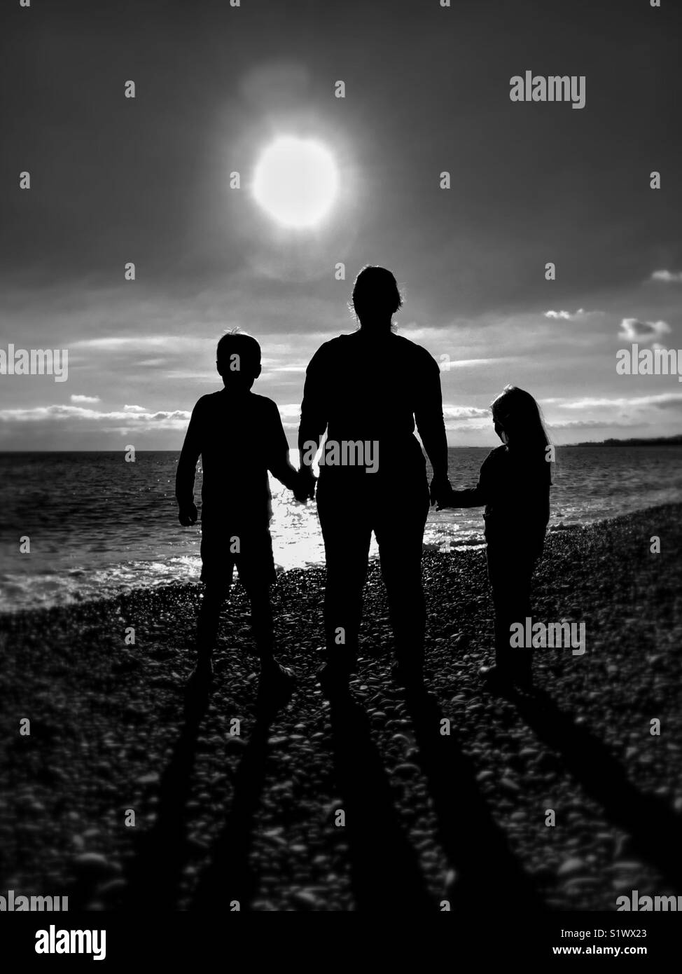 A mother/wife/lone parent holds the hands of (her?) 2 children as they stand on a beach & gaze into the bright light/sunshine(?) Stock Photo