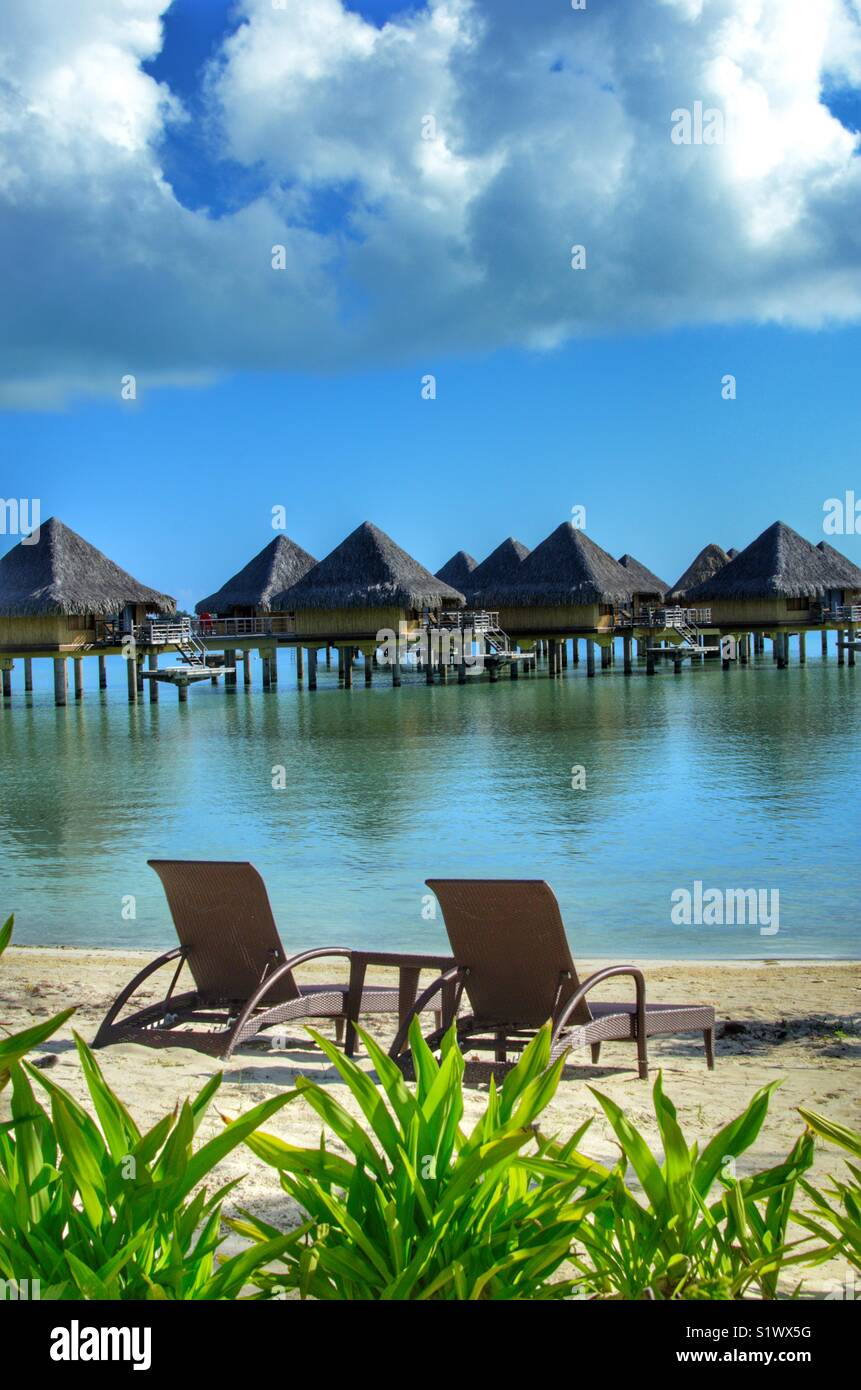 Lounge chairs on the beach in Bora Bora, French Polynesia in the South Pacific. Over the water bungalows used by - Stock Image