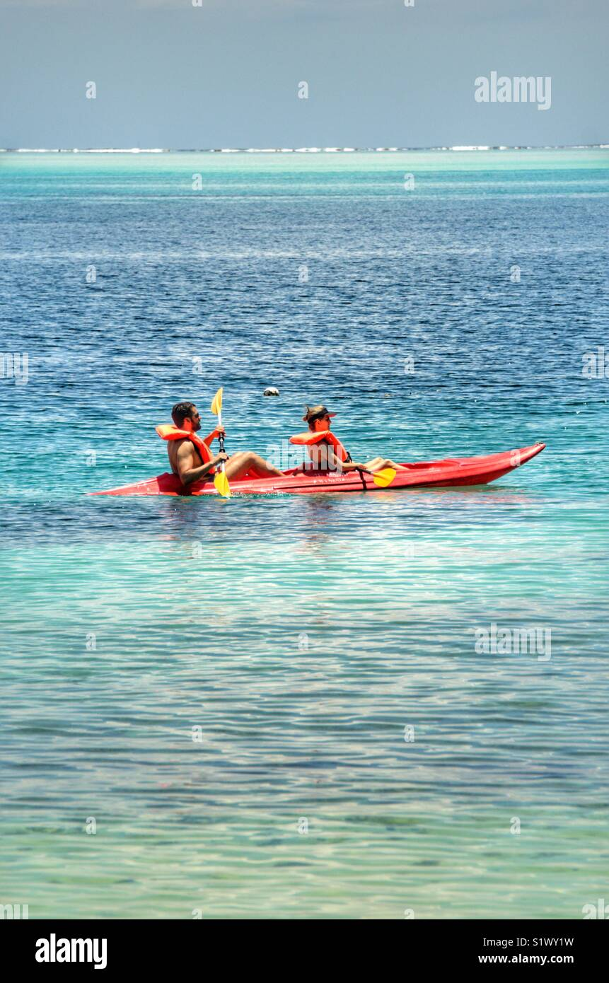 Couple in a kayak paddling around the lagoon in Bora-Bora, French Polynesia, in the South Pacific, - Stock Image