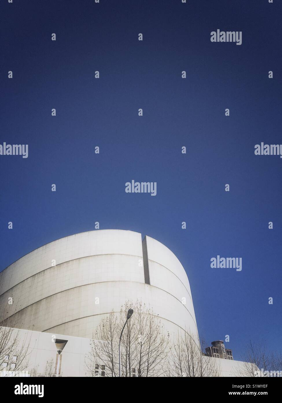 Top of round building against blue sky - Stock Image