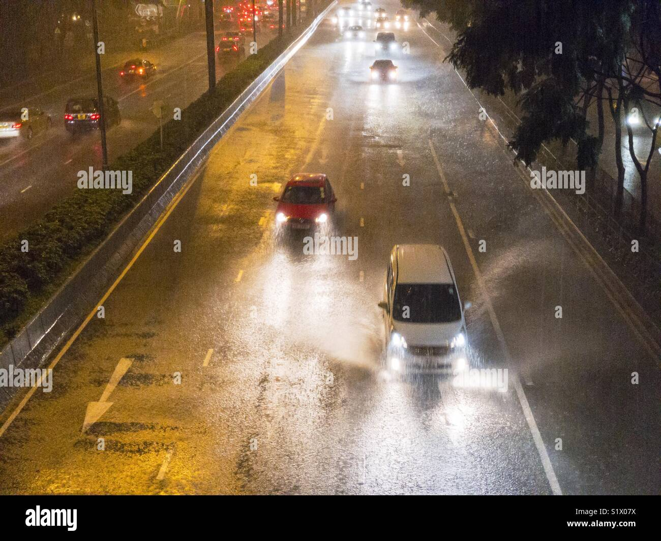 Blurred motion of car on street during rainy - Stock Image