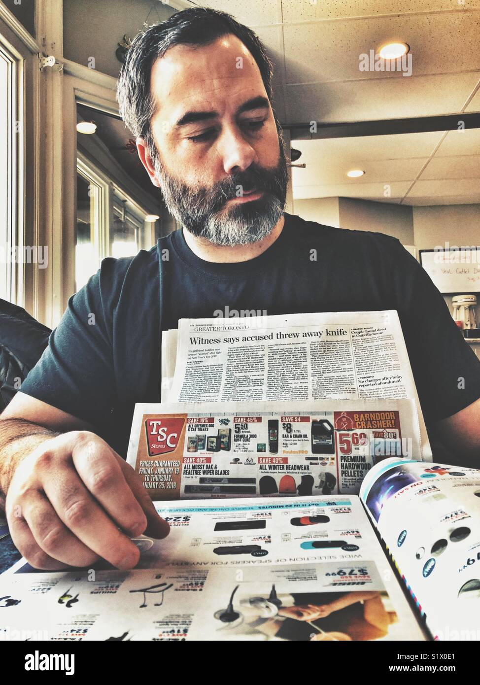 Middle aged man with beard reading a newspaper in a diner - Stock Image