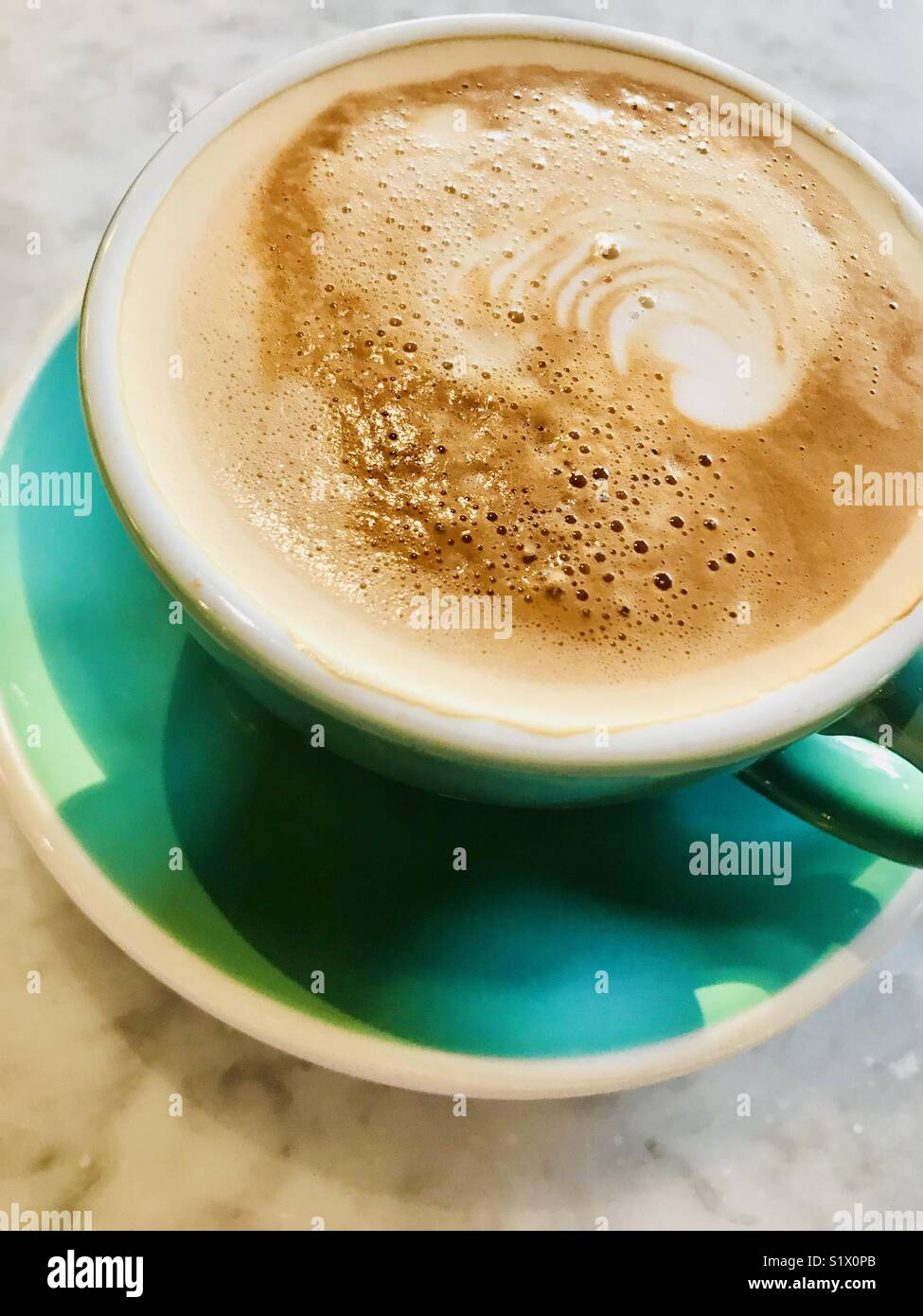 Flat white coffee served in a green cup - Stock Image