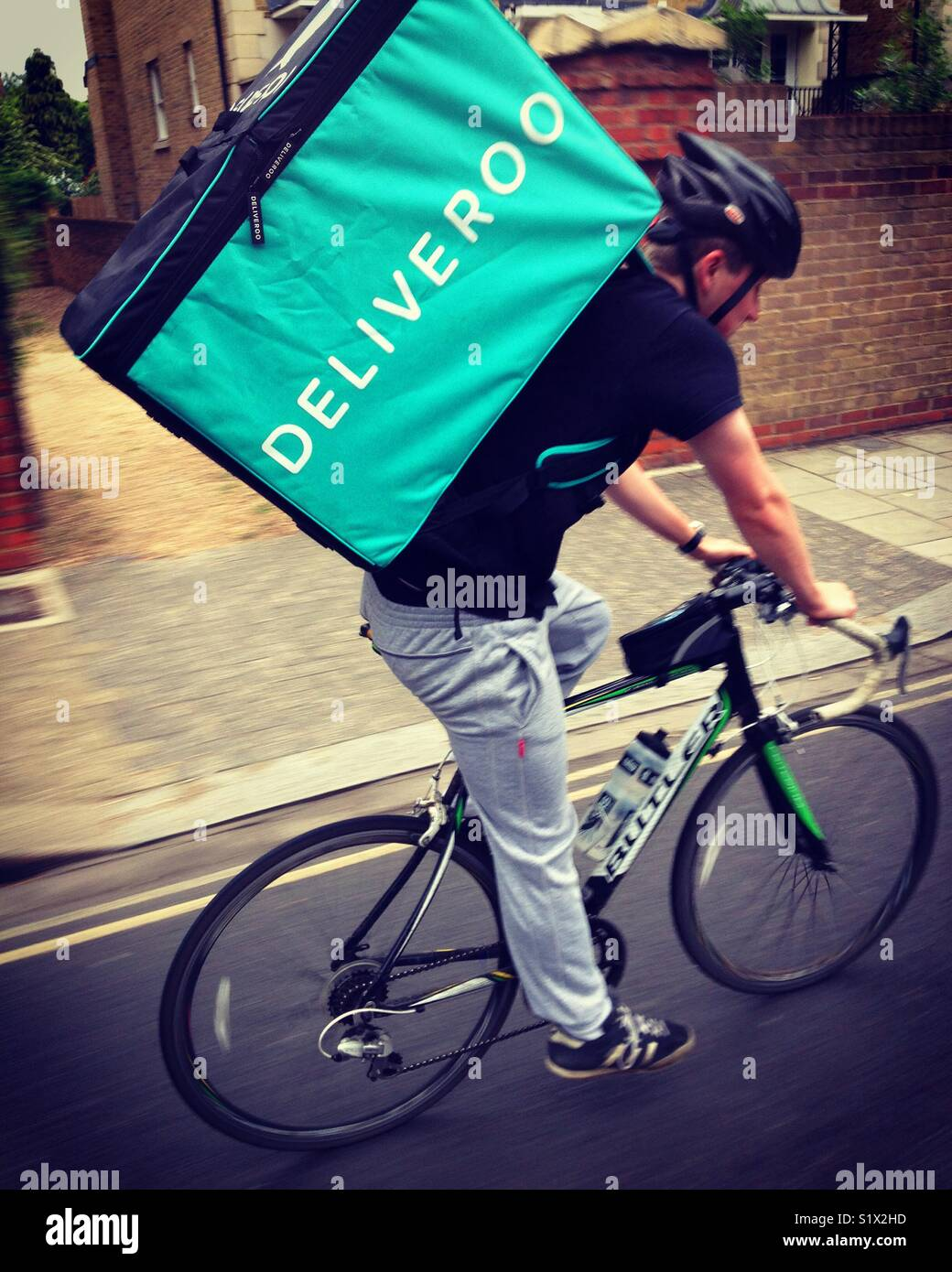 91a8a03dc19 Deliveroo cyclist courier delivering a takeaway / take away meal / food to  a client at