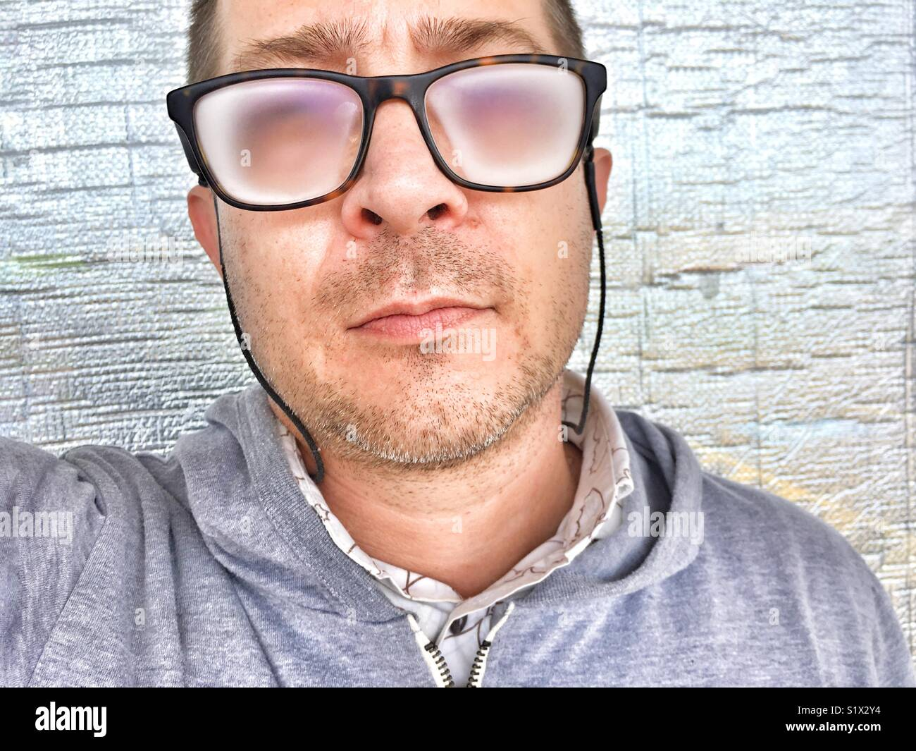 Headshot of a man, unshaven and wearing fogged up eyeglasses. - Stock Image