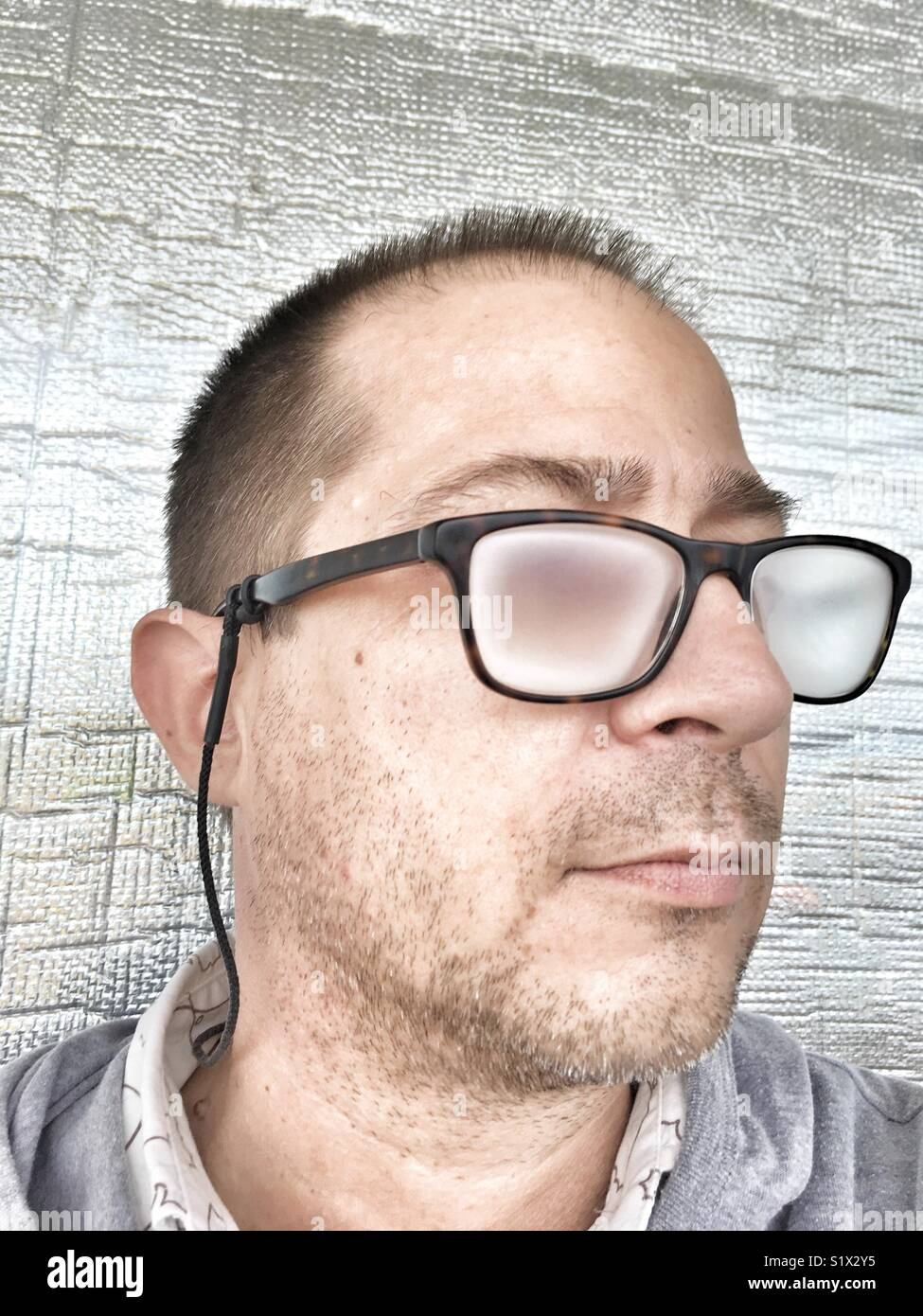 Portrait of a man, unshaven and wearing fogged up prescription glasses. - Stock Image
