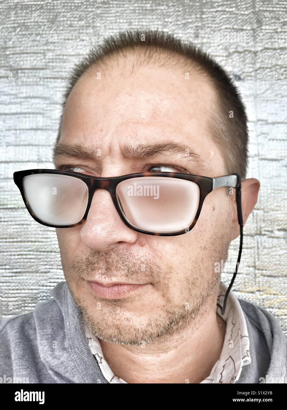Portrait of a man, unshaven and wearing fogged up eyeglasses. - Stock Image