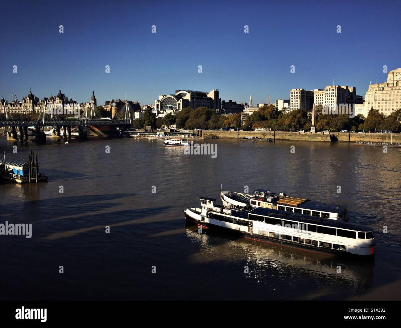A pleasure boat sails down the river Thames in London Stock Photo