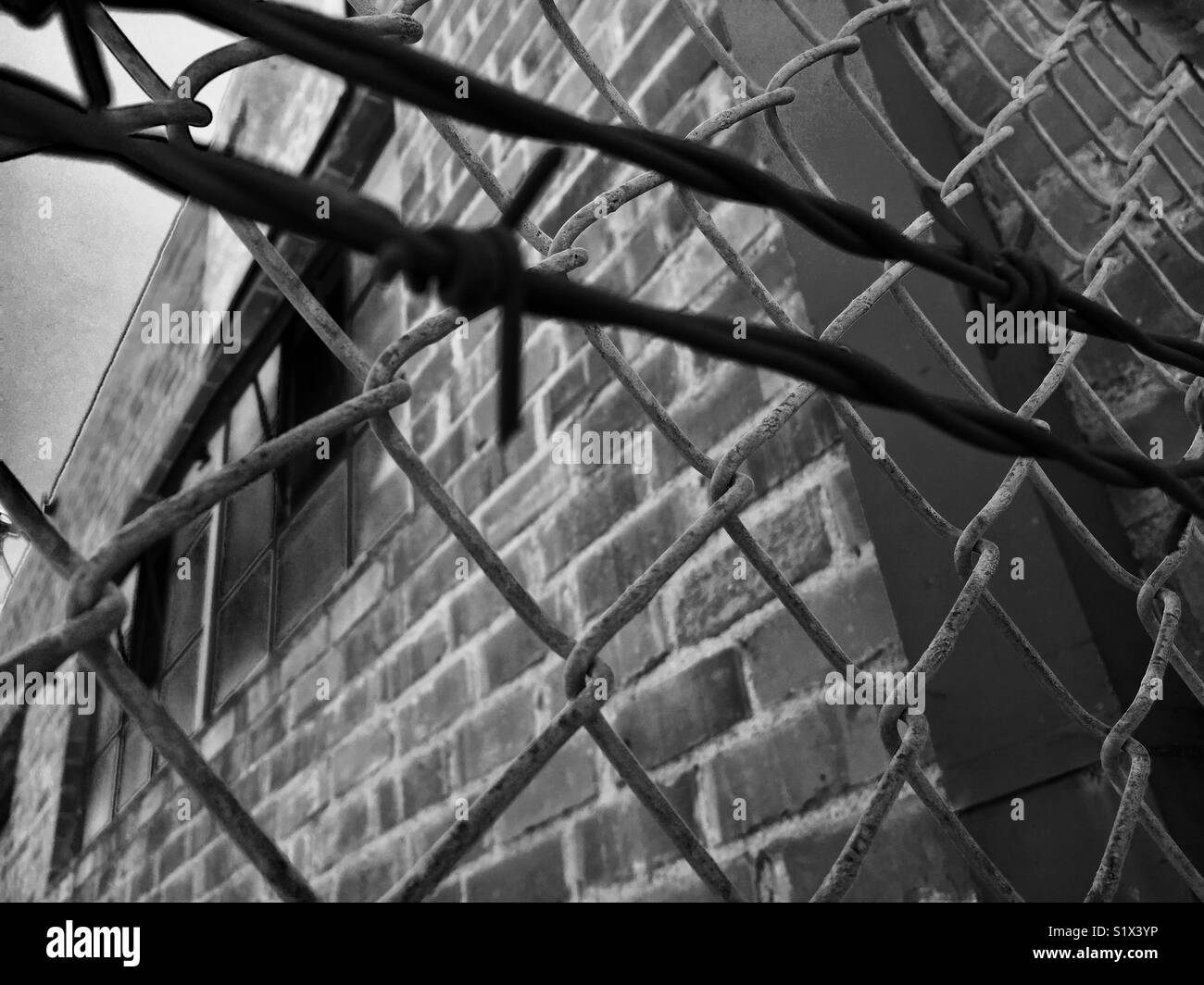 Brick building with barb wire Stock Photo: 310975162 - Alamy