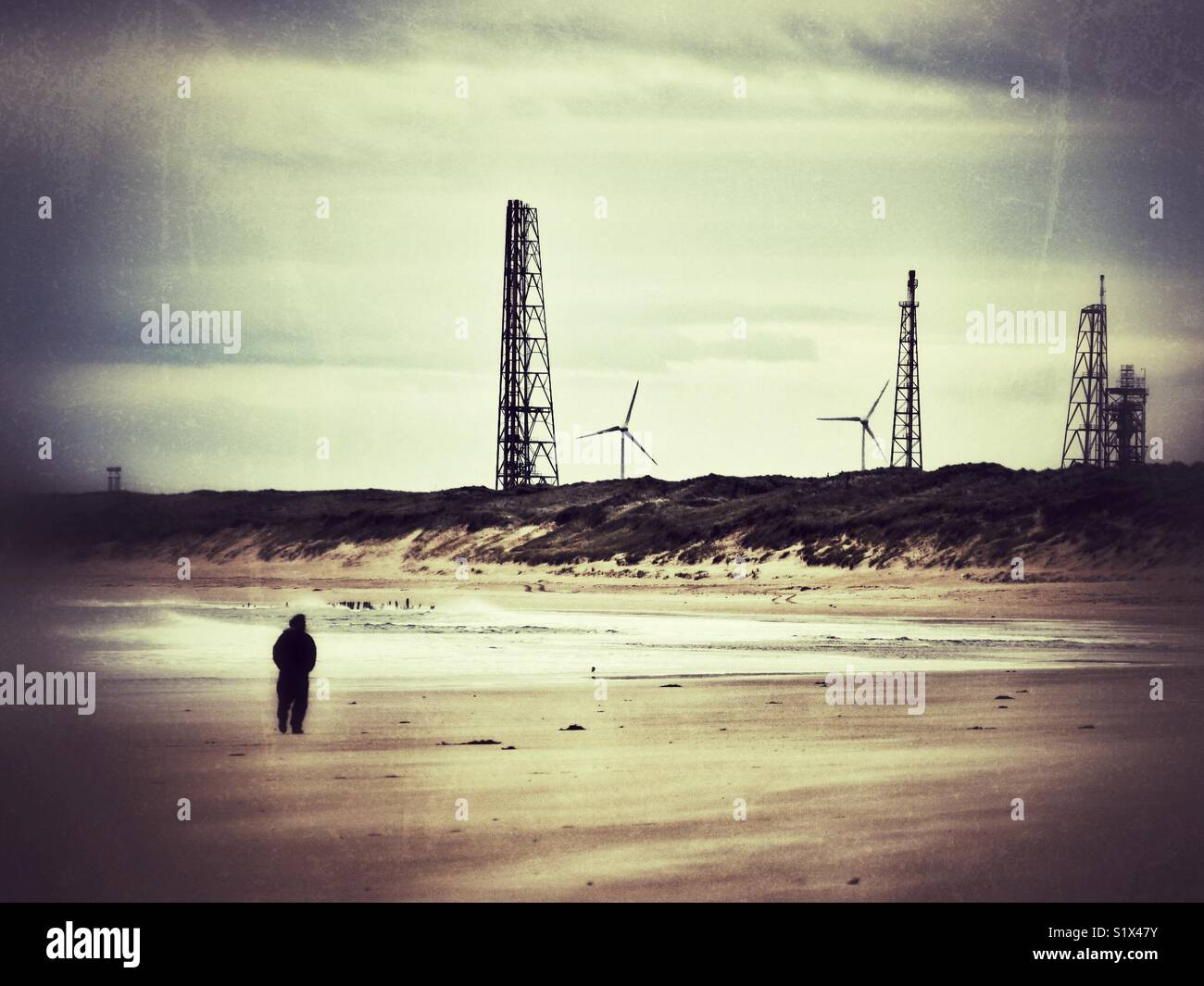 Beach view with industrial background of drilling and wind turbines. Stock Photo