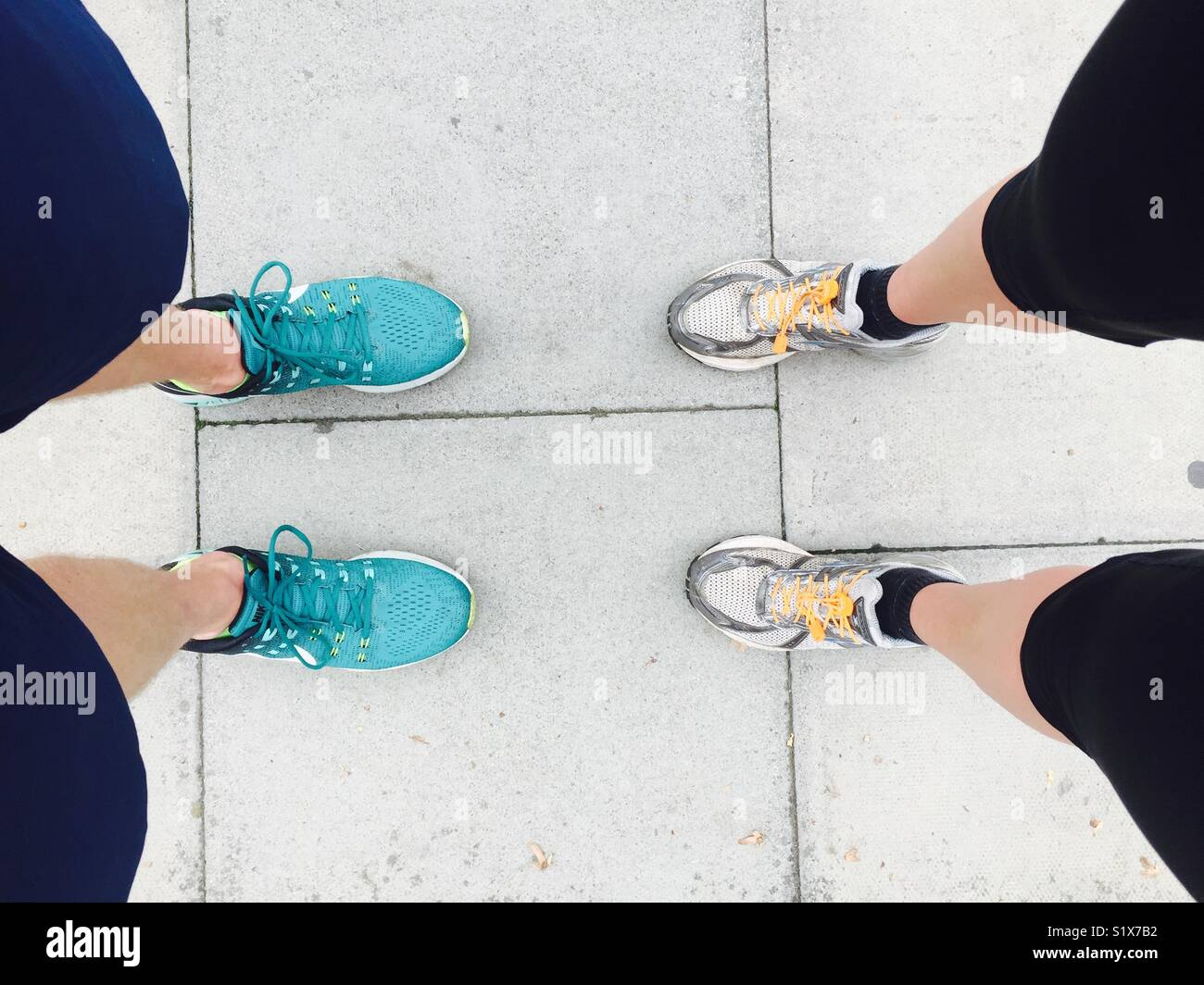 Looking down on two pairs of legs and feet - Stock Image
