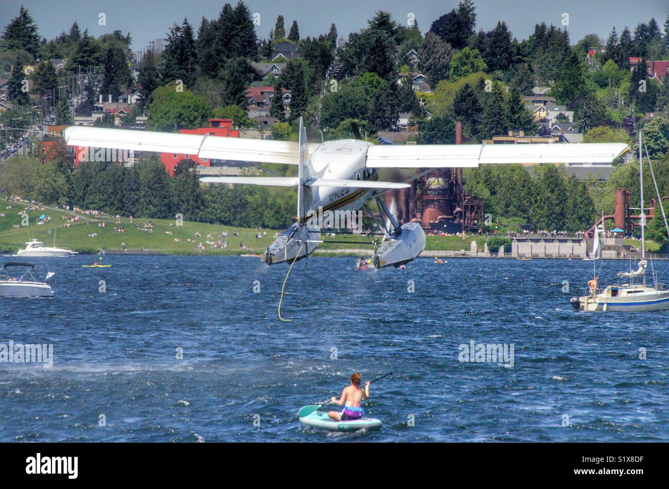 Seaplane taking off on Lake Union over the top of a kayaker - Stock Image