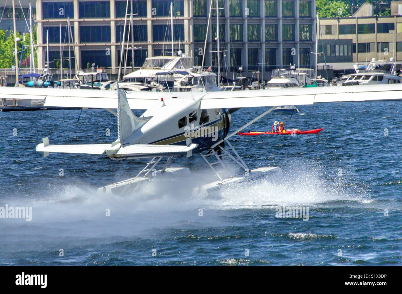 Kayaking in front of a float plane on Lake Union in Seattle Washington - Stock Image