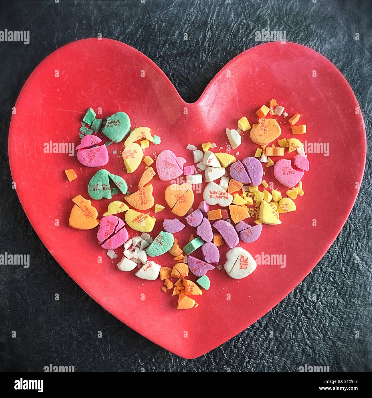 Broken candy hearts on a plate. - Stock Image