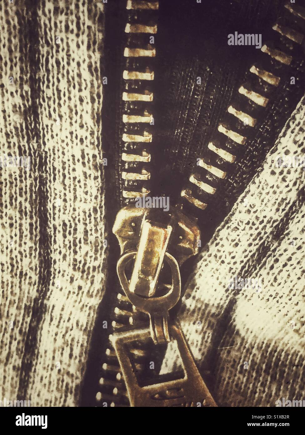 Closeup of brass coloured zipper partially unzipped with grey and black fabric - Stock Image