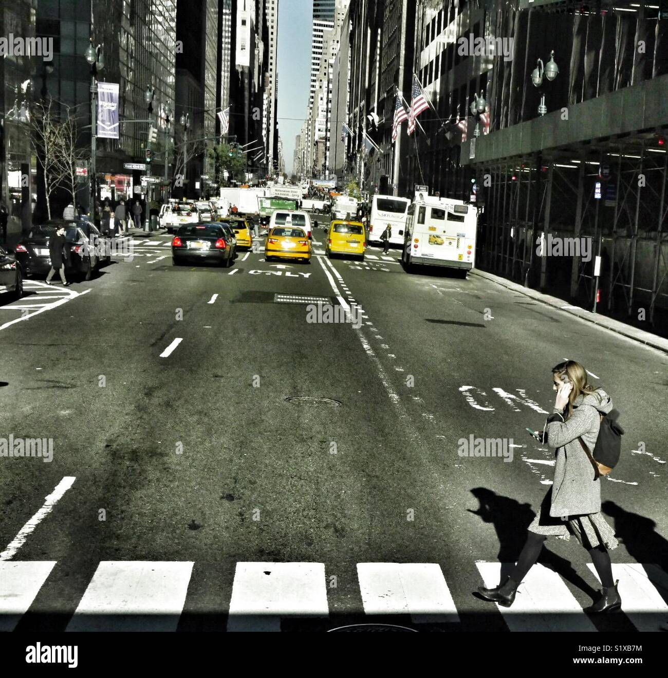 New York City street scene with girl on the phone crossing the road, NY, USA. Stock Photo