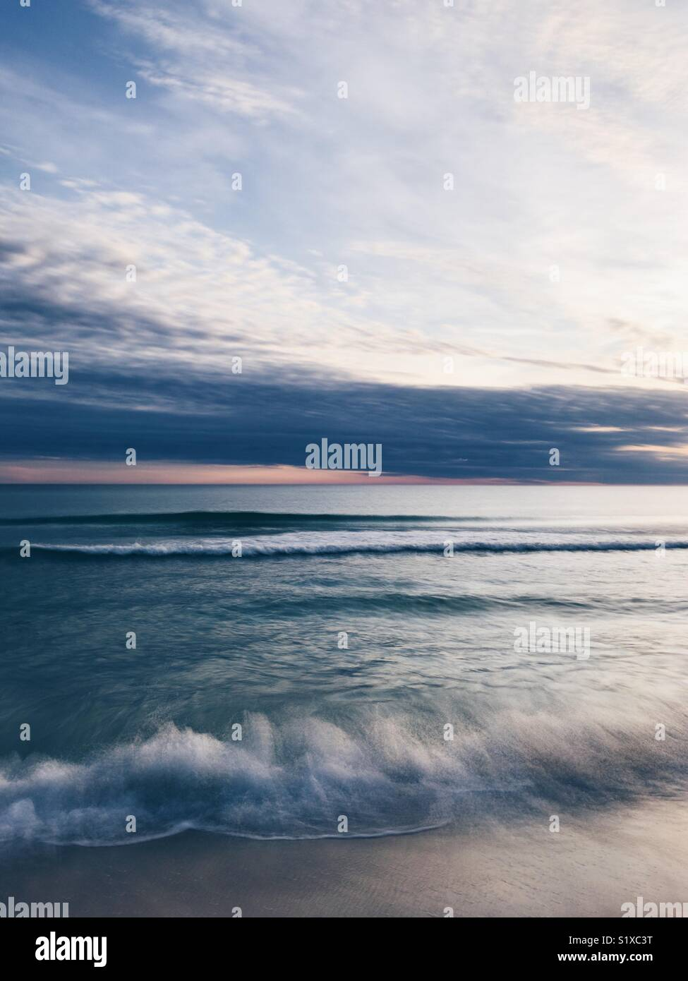 Long exposure of waves lapping on a beach in Florida on the coast of the Gulf of Mexico. - Stock Image