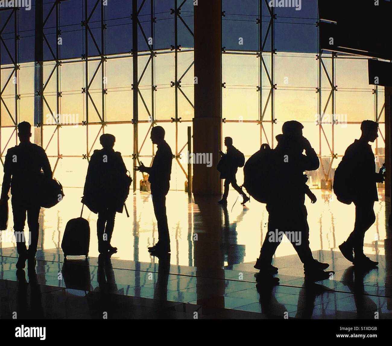 Busy airport scene,  Barcelona EL Prat airport terminal 2, early morning commuters in silhouette, 2017 - Stock Image