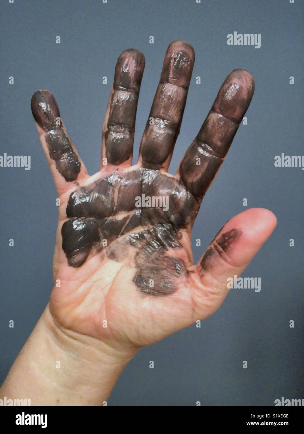 An outstretched hand smudged and covered with paint Stock Photo