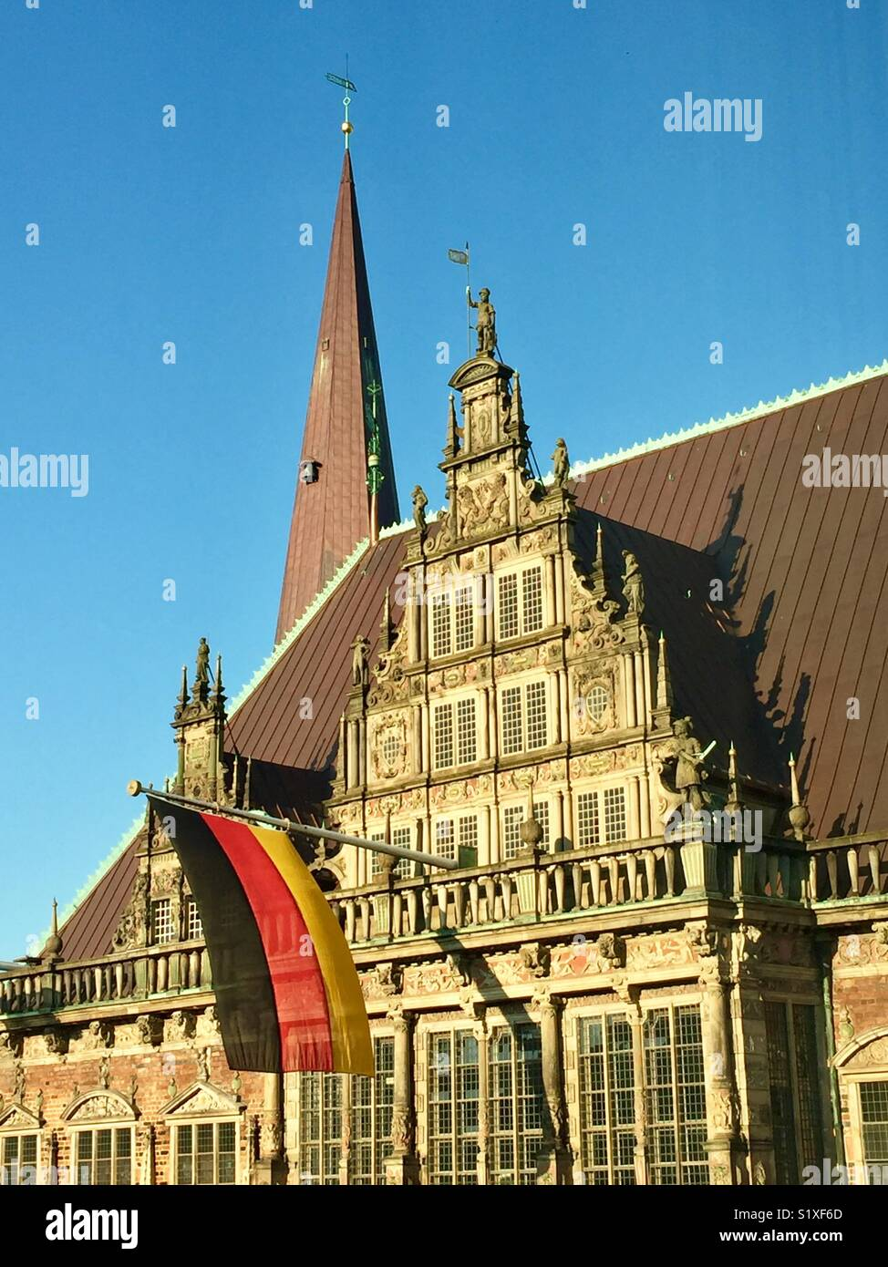 A view of the flemish gable of the Bremen Town Hall added about 1612 flying the German flag.  An important example - Stock Image