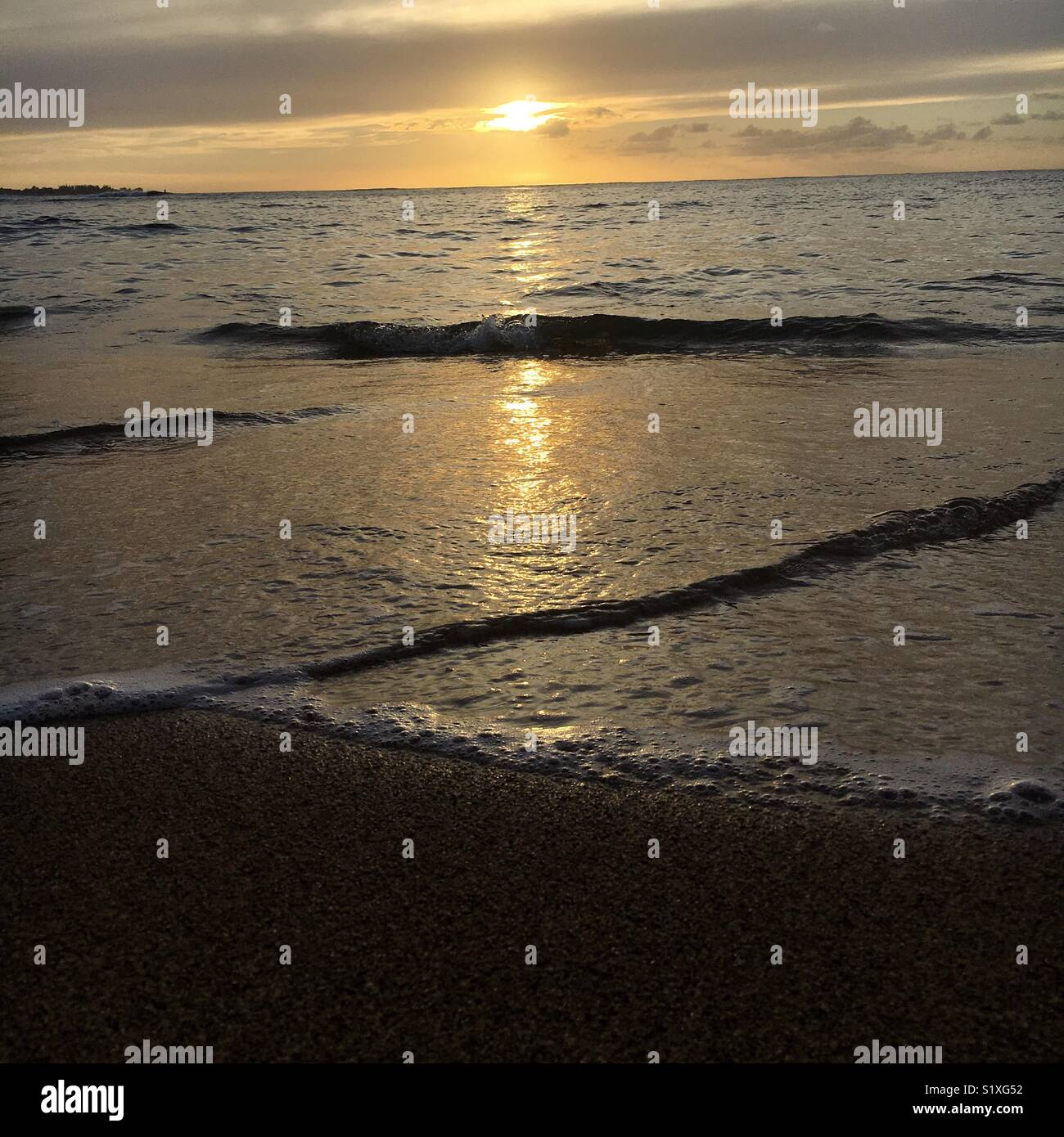 Small gentle waves glide onto shore - Stock Image