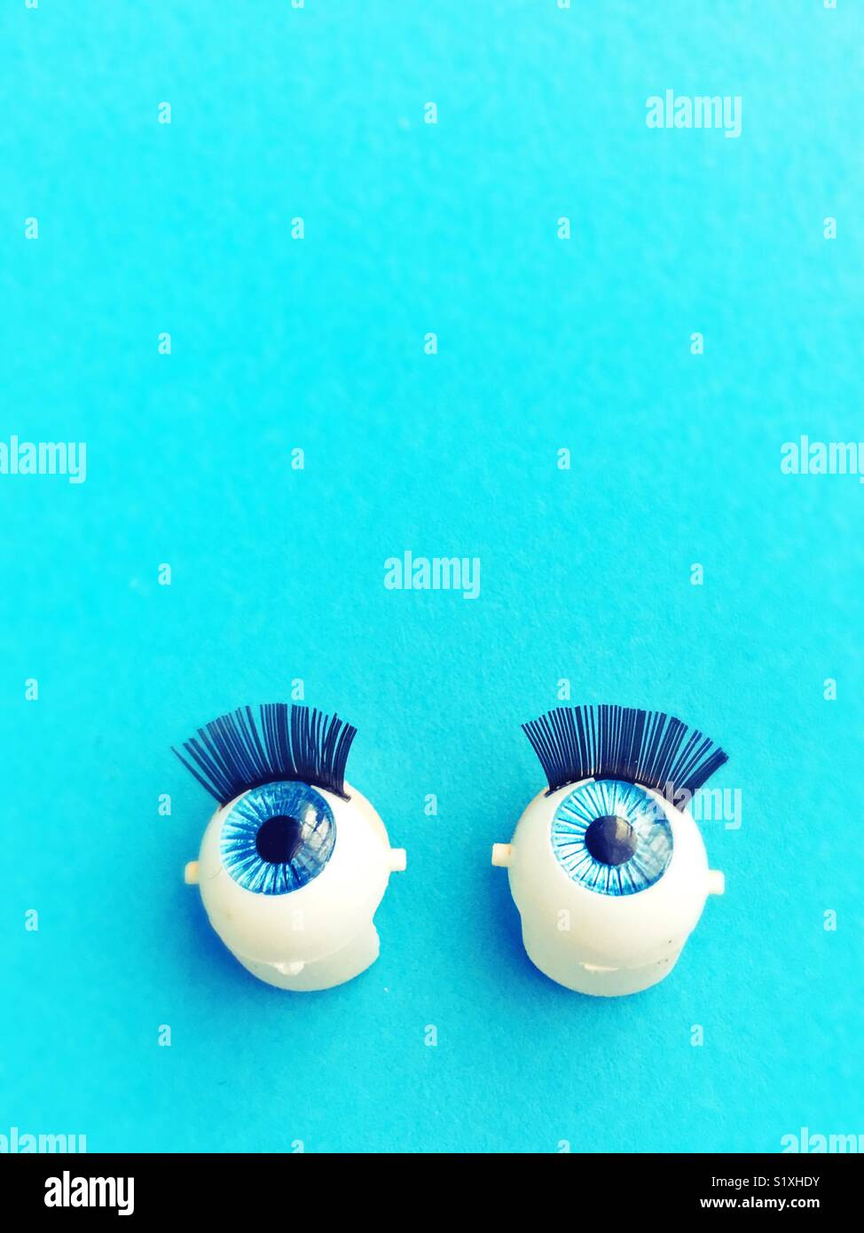 A set of blue doll eyes. - Stock Image