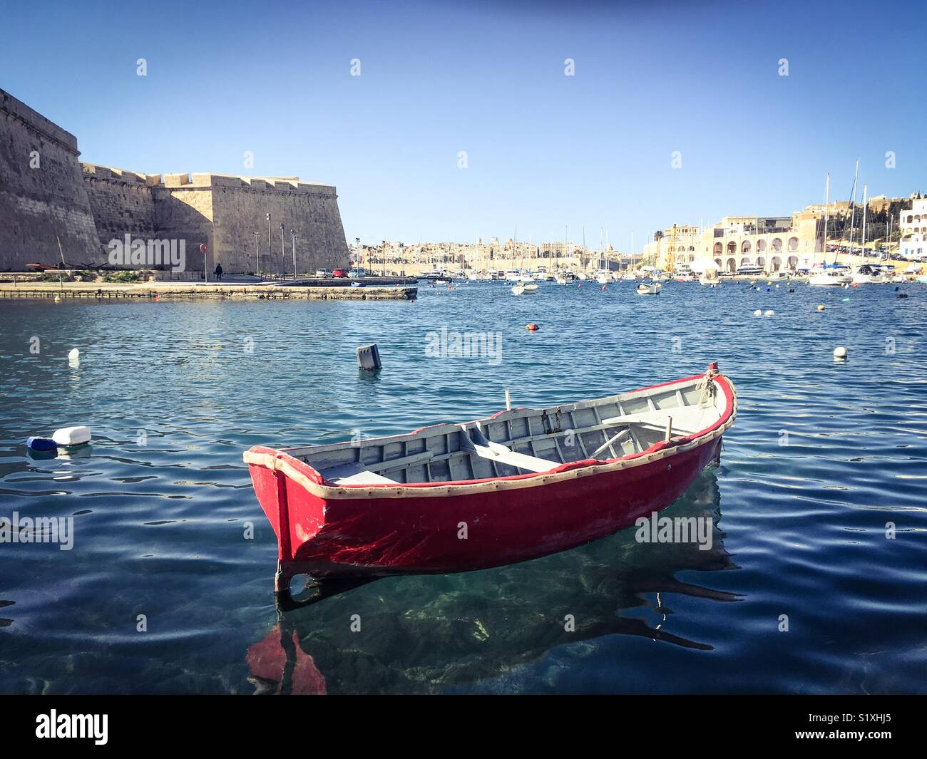 Small red wooden fishing boat in the bay, Kalkara, Malta - Stock Image