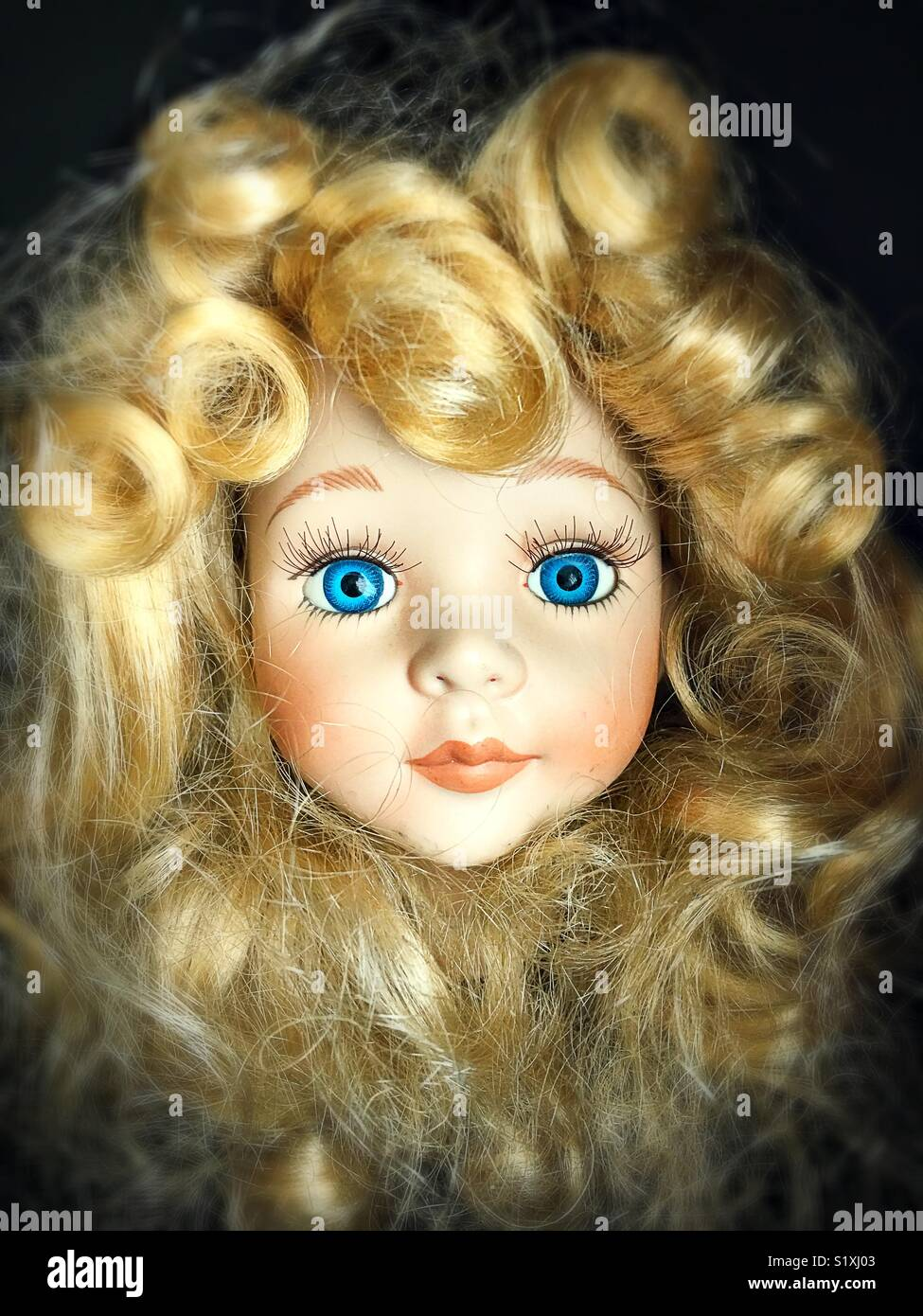 Doll head with blonde curls and blue eyes. - Stock Image