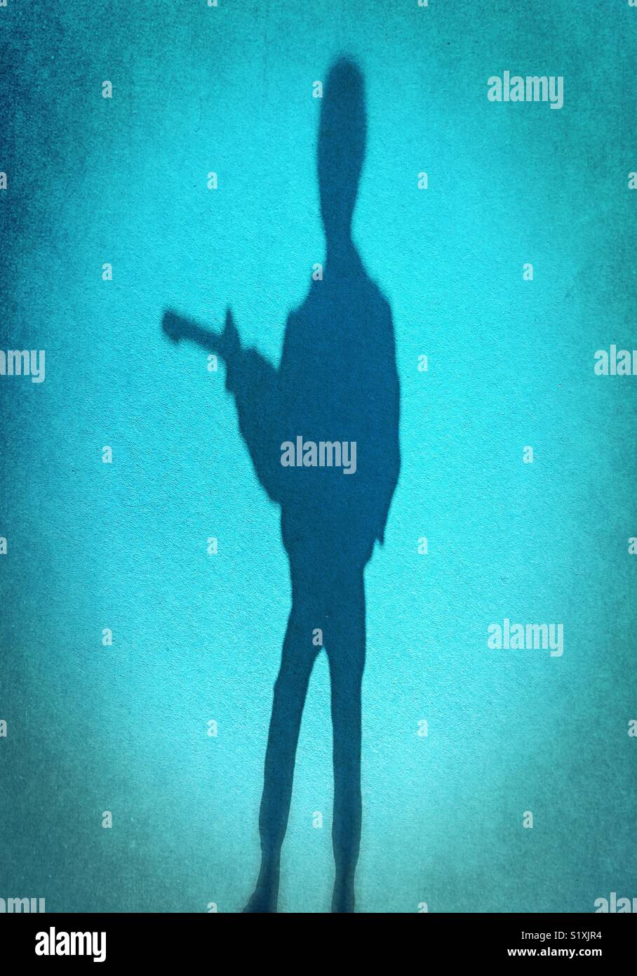 Silhouette figure of person with gun. - Stock Image