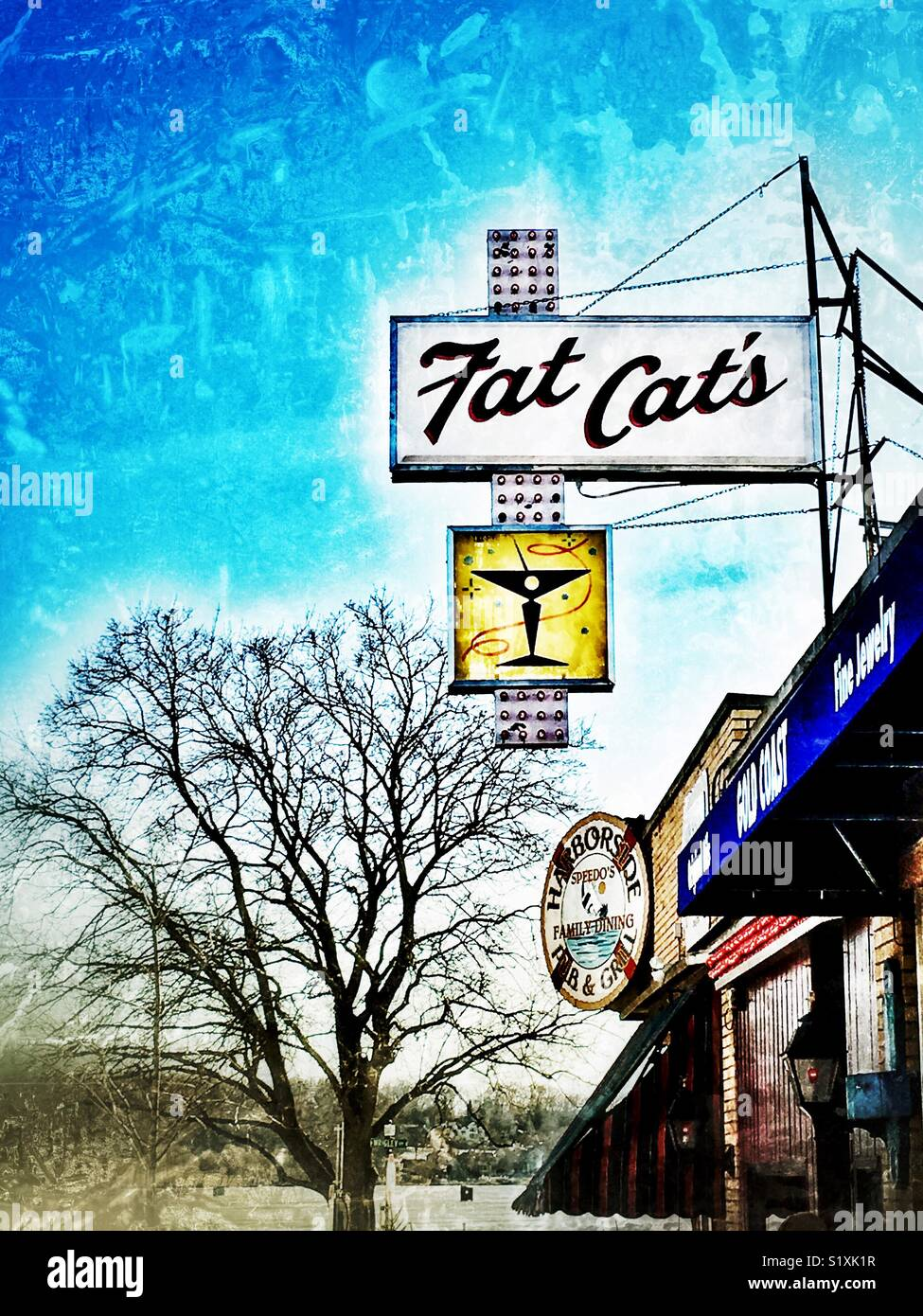 Billboard for Fat Cats bar alongside gift shop and Harborside Pub & Gill in downtown Lake Geneva, WI - Stock Image