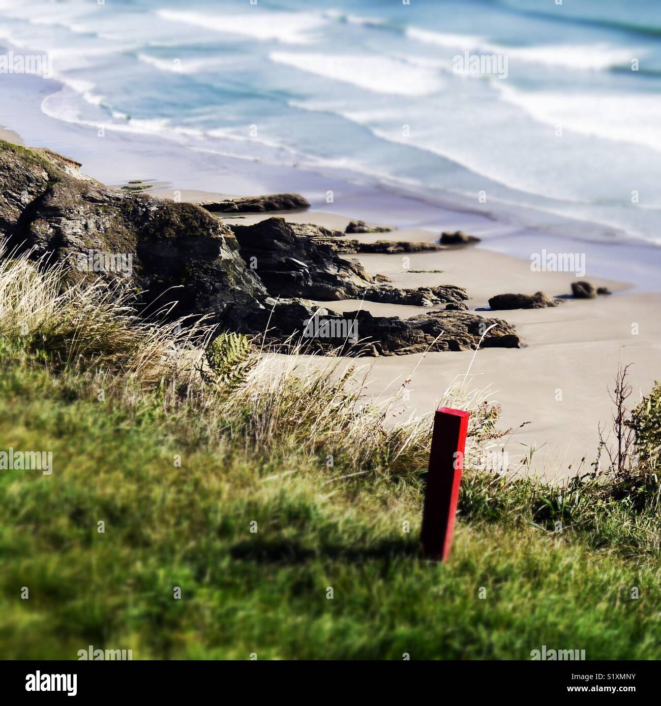 Red post on edge of public footpath along a coastal path. Stock Photo