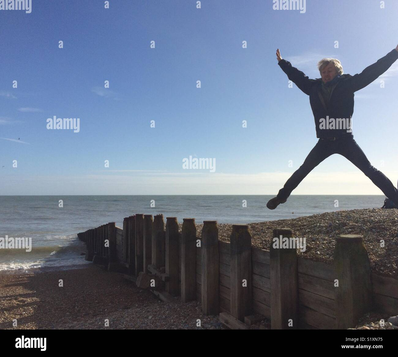 Man jumping on beach - Stock Image