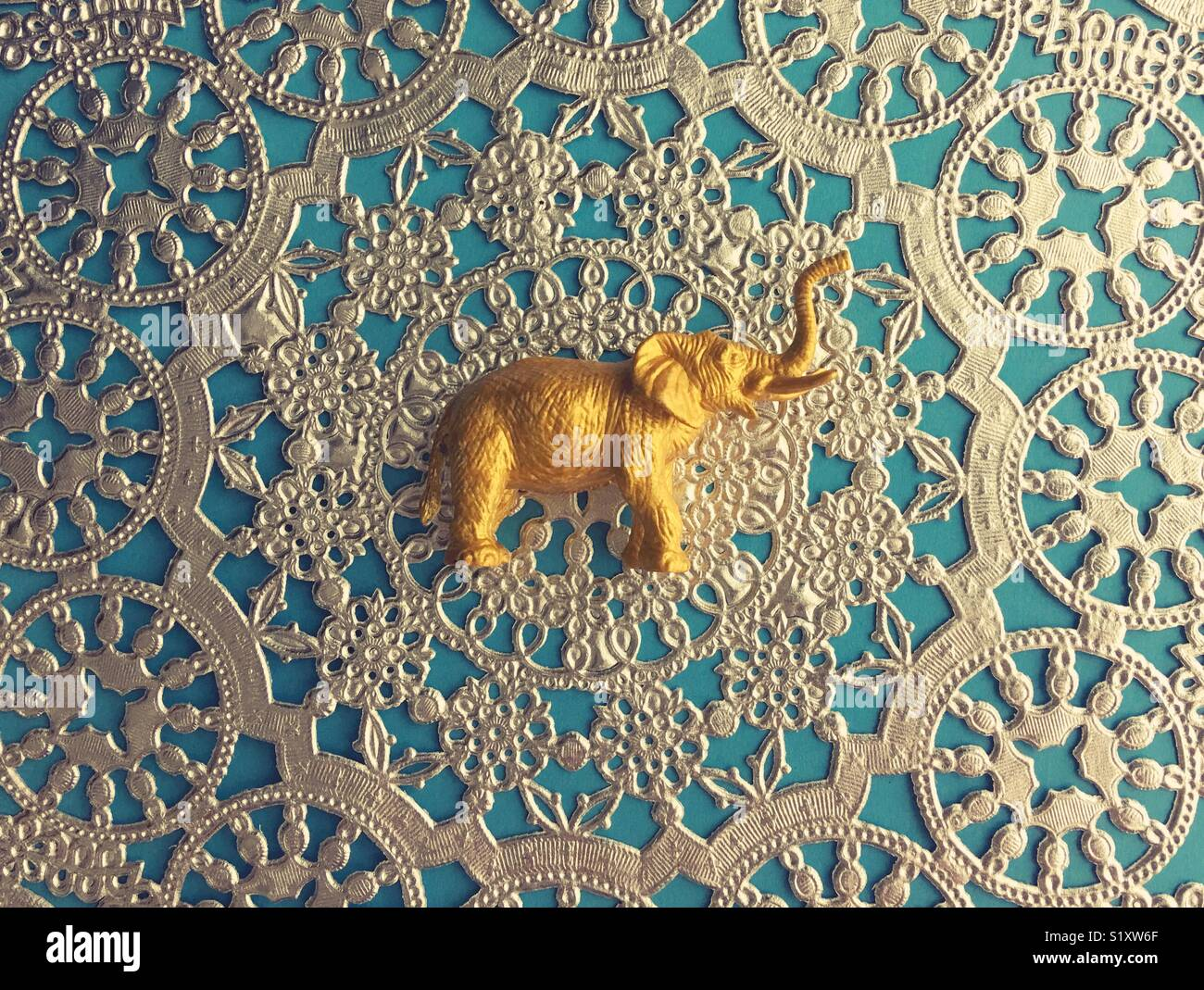 A gold elephant figurine against an ornate background. - Stock Image