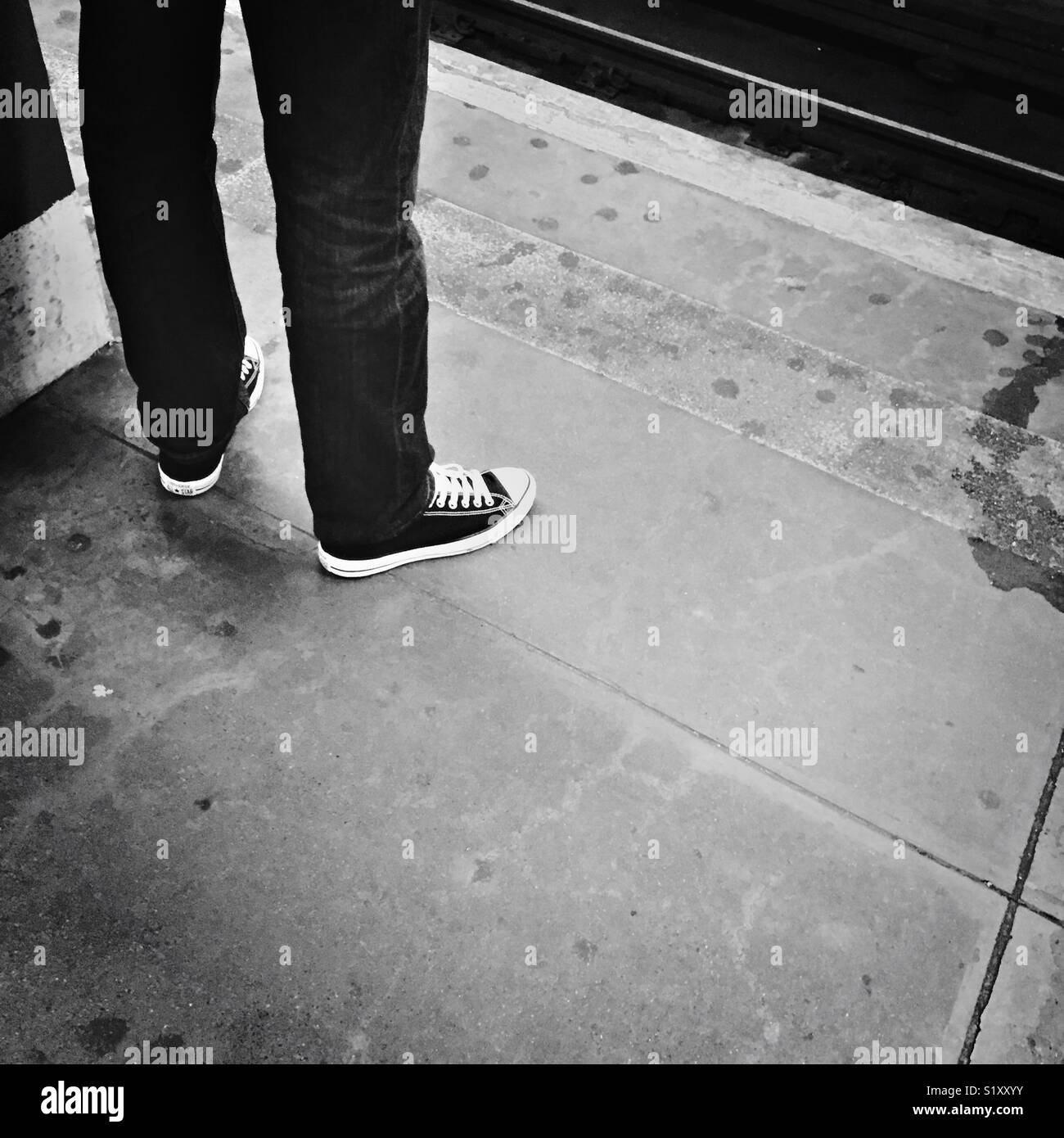 a74bb057651 A man in jeans and Converse Chuck Taylor sneakers stands on a New York City  subway