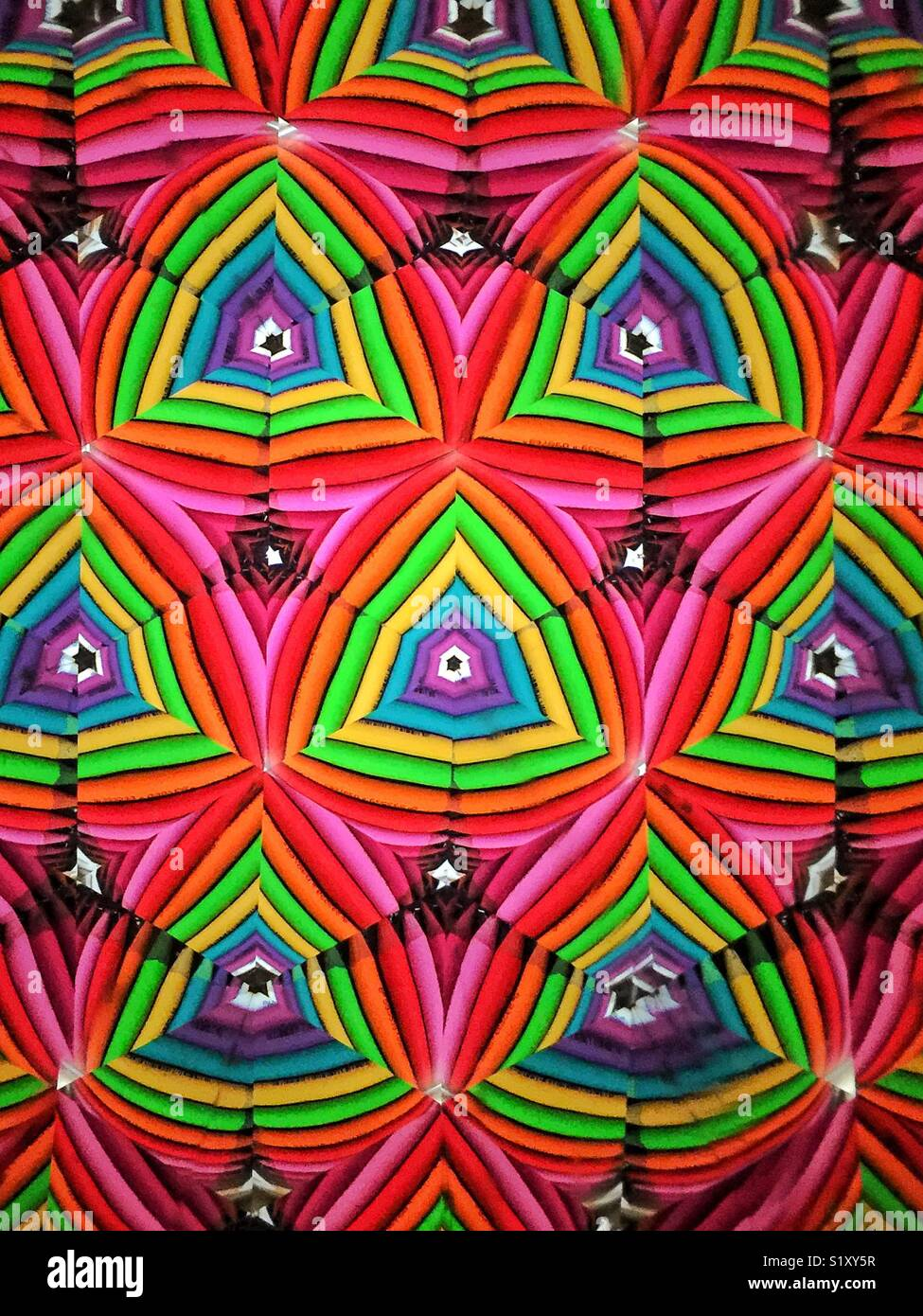 colored pencils in rainbow colors as seen through kaleidoscope - Stock Image