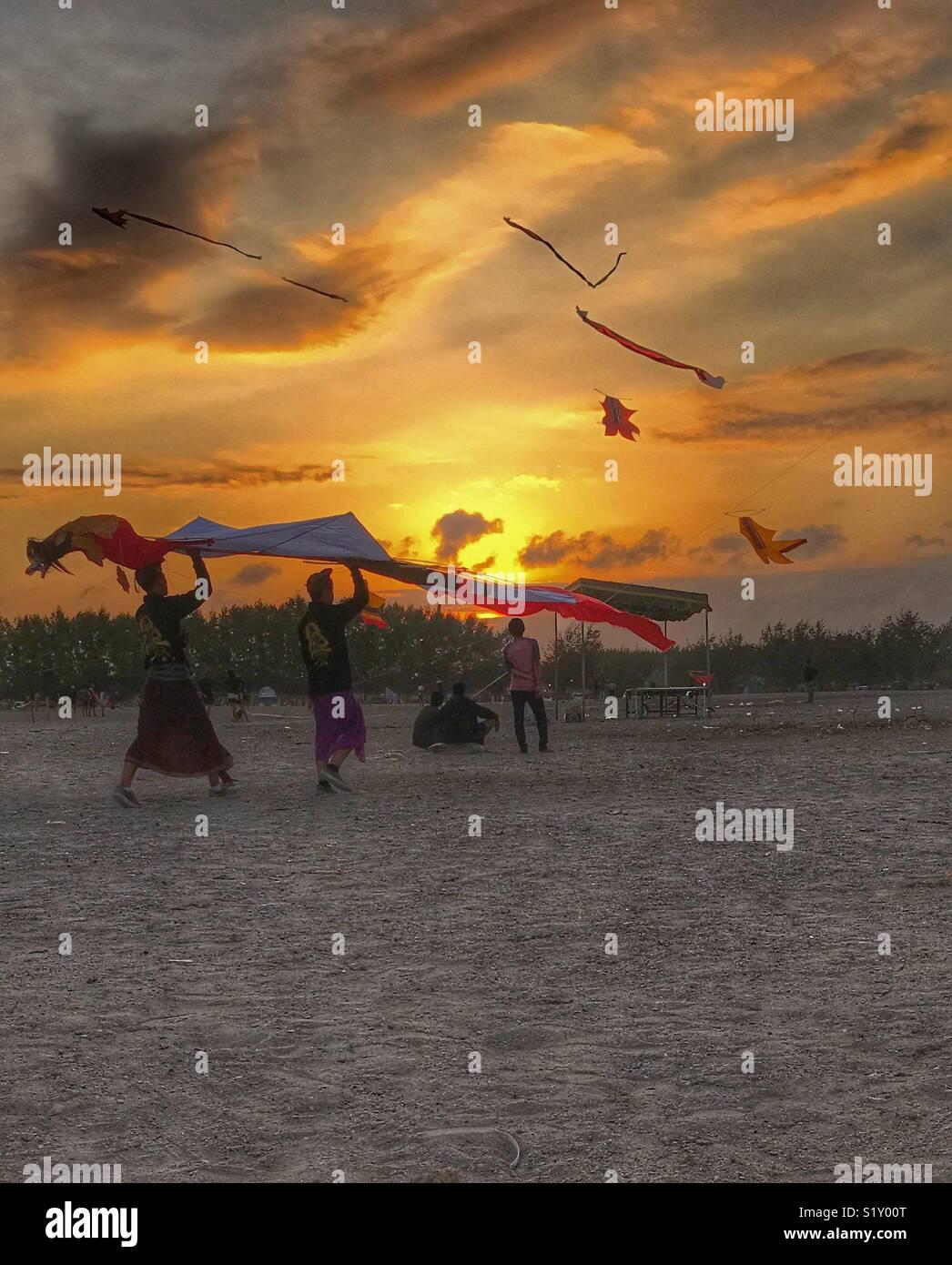 Flying kites at dusk - Stock Image