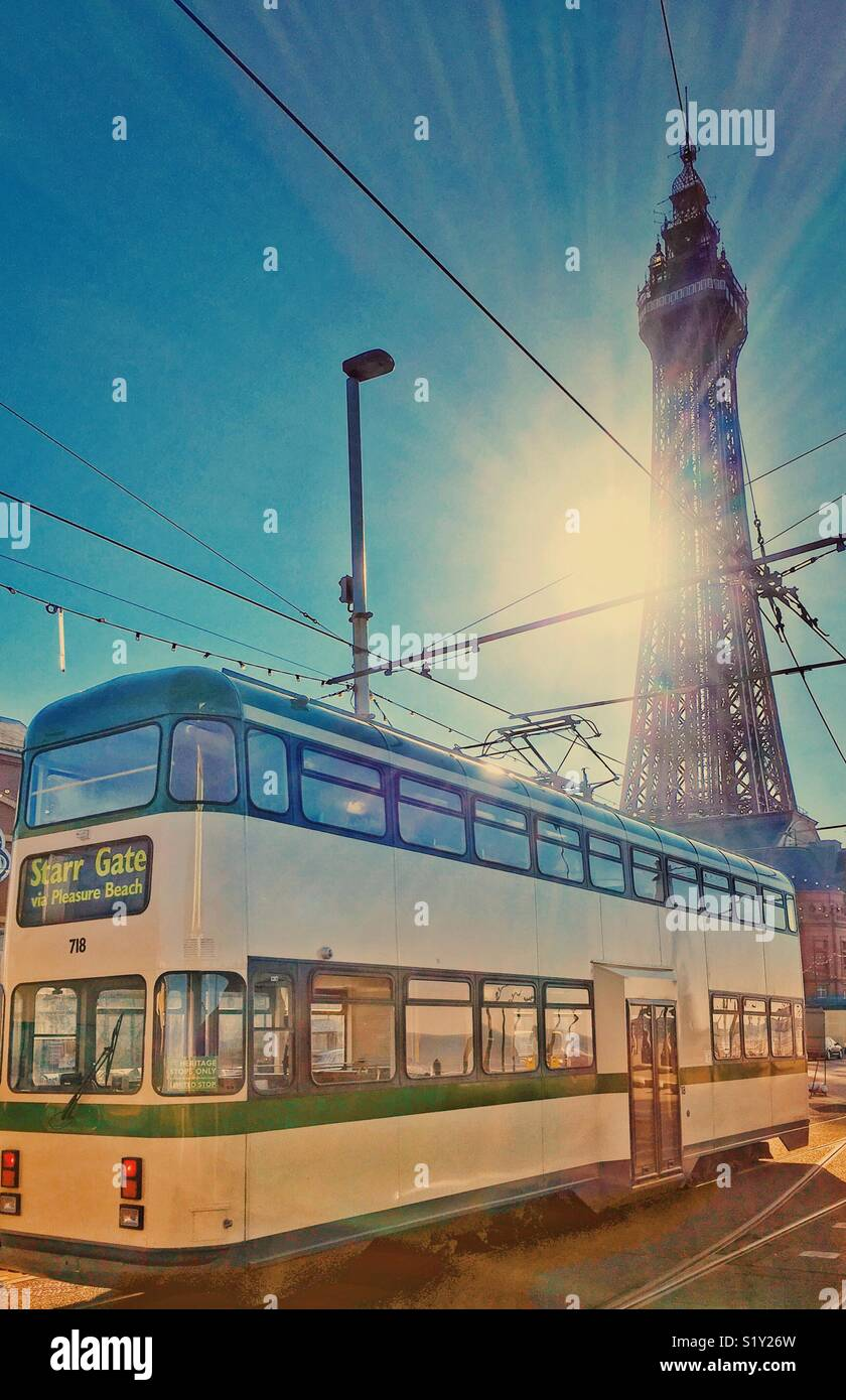 Blackpool Tower and vintage tram with the sun bursting from behind the Tower - Stock Image