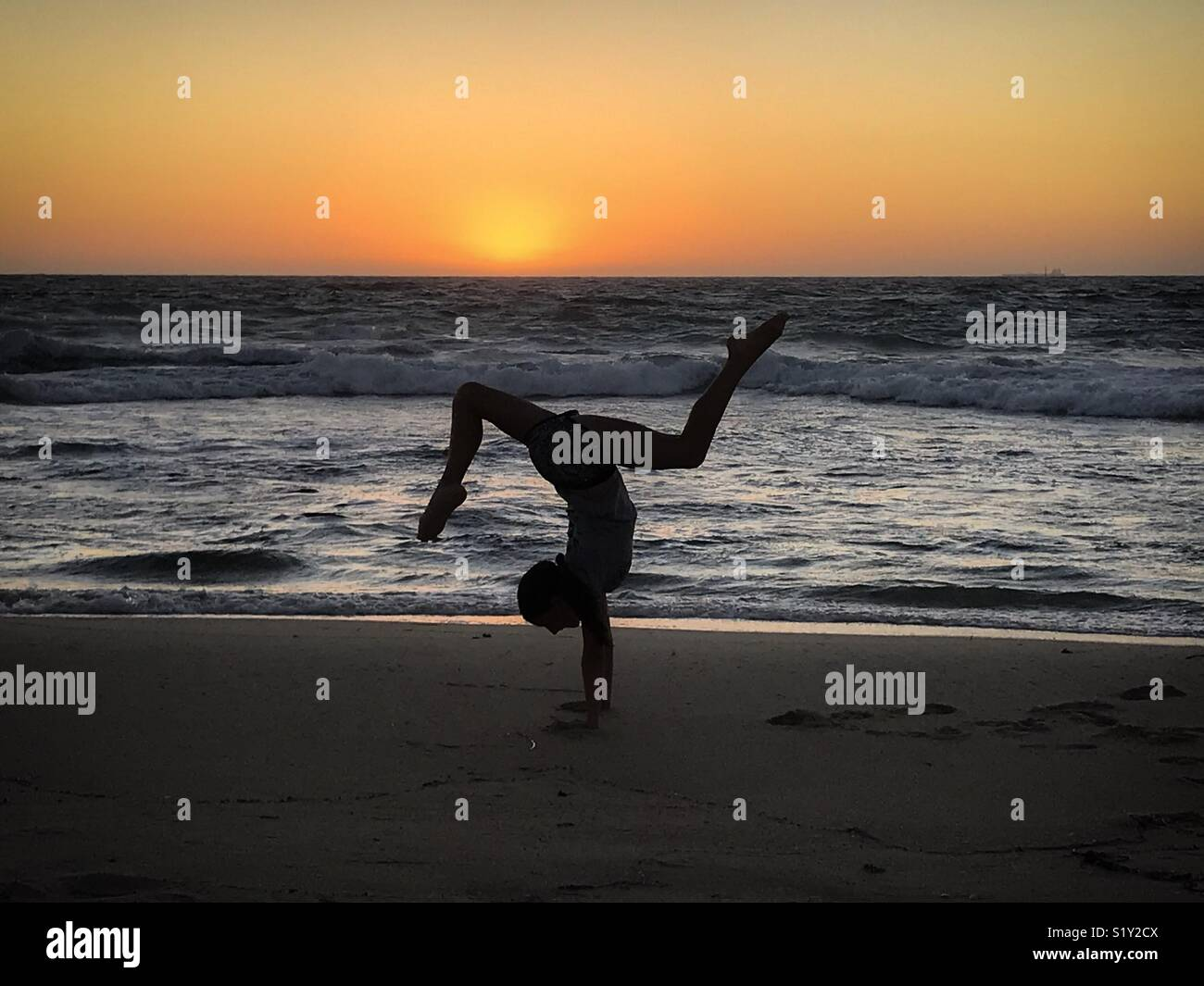 Girl doing handstand during beach sunset - Stock Image