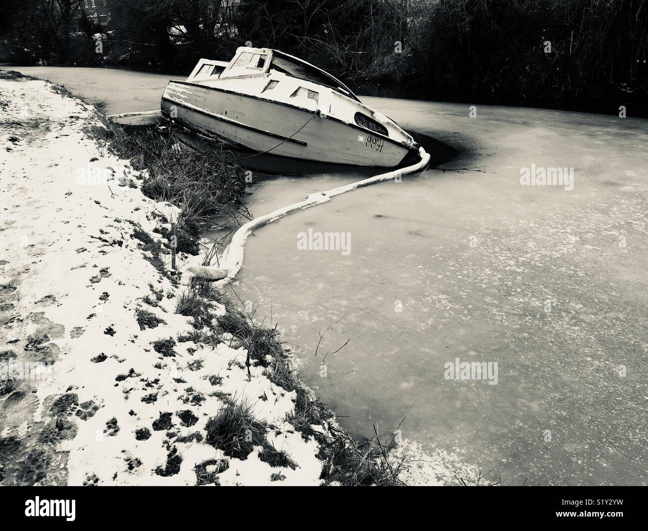 A boat that has fallen over and frozen in the ice on the river - Stock Image