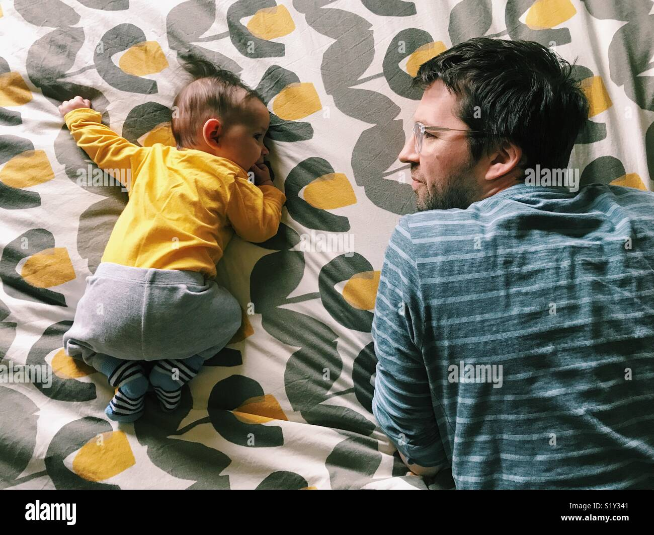 Tummy time for a baby girl with her father watching beside her. - Stock Image