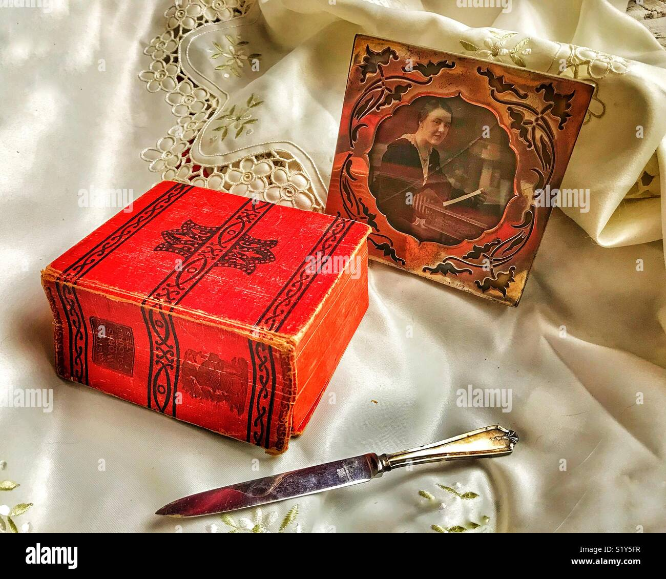 Still life antique arrangement of a silver photo frame, a silver letter opener and a book of Aristotle's Works Stock Photo