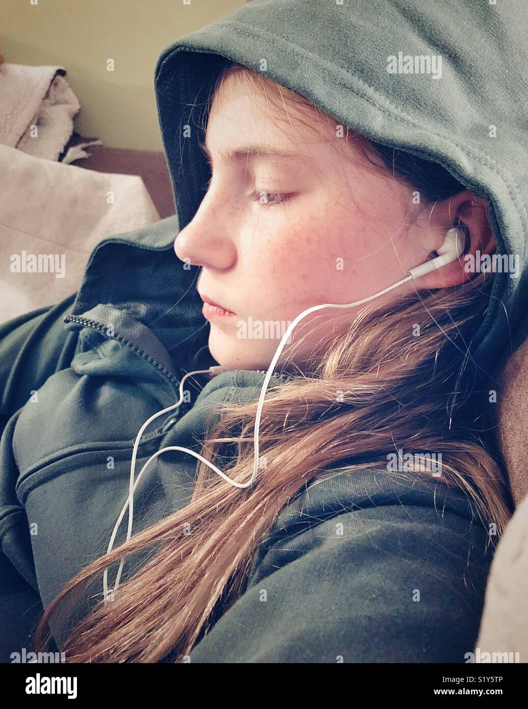 Profile image of young teen girl with long blonde hair looking down wearing white earbuds and a green hood - Stock Image