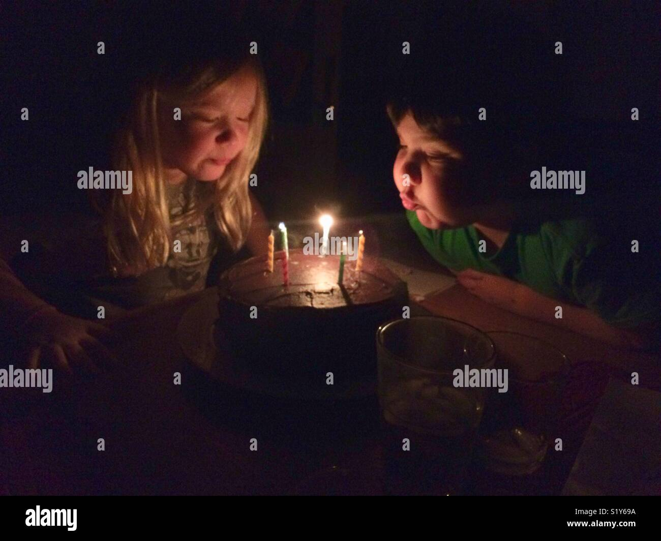 Boy Blowing Out Candles On His Birthday Cake Stock Photos & Boy