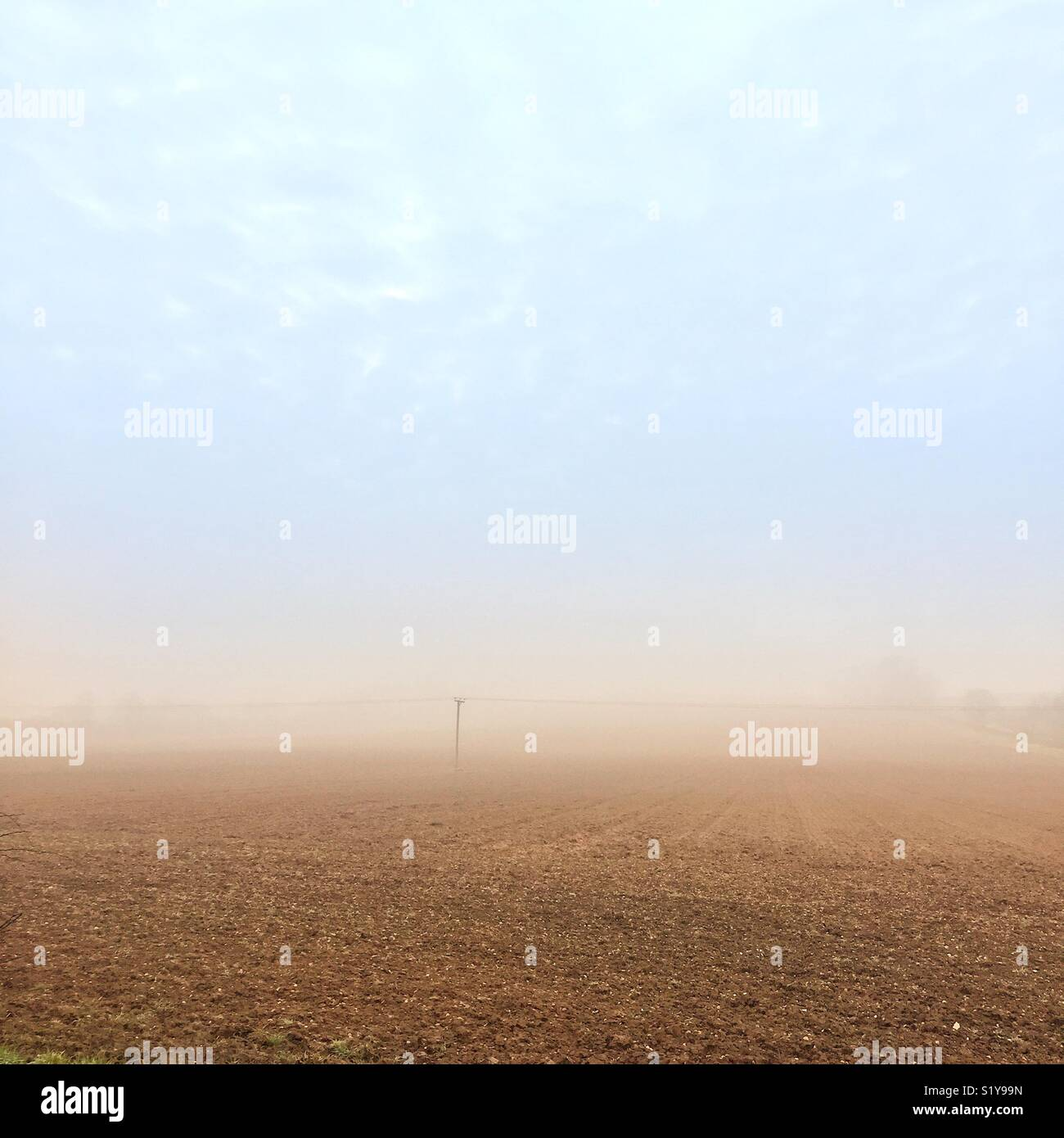 Overhead lines and pole in a foggy field. - Stock Image