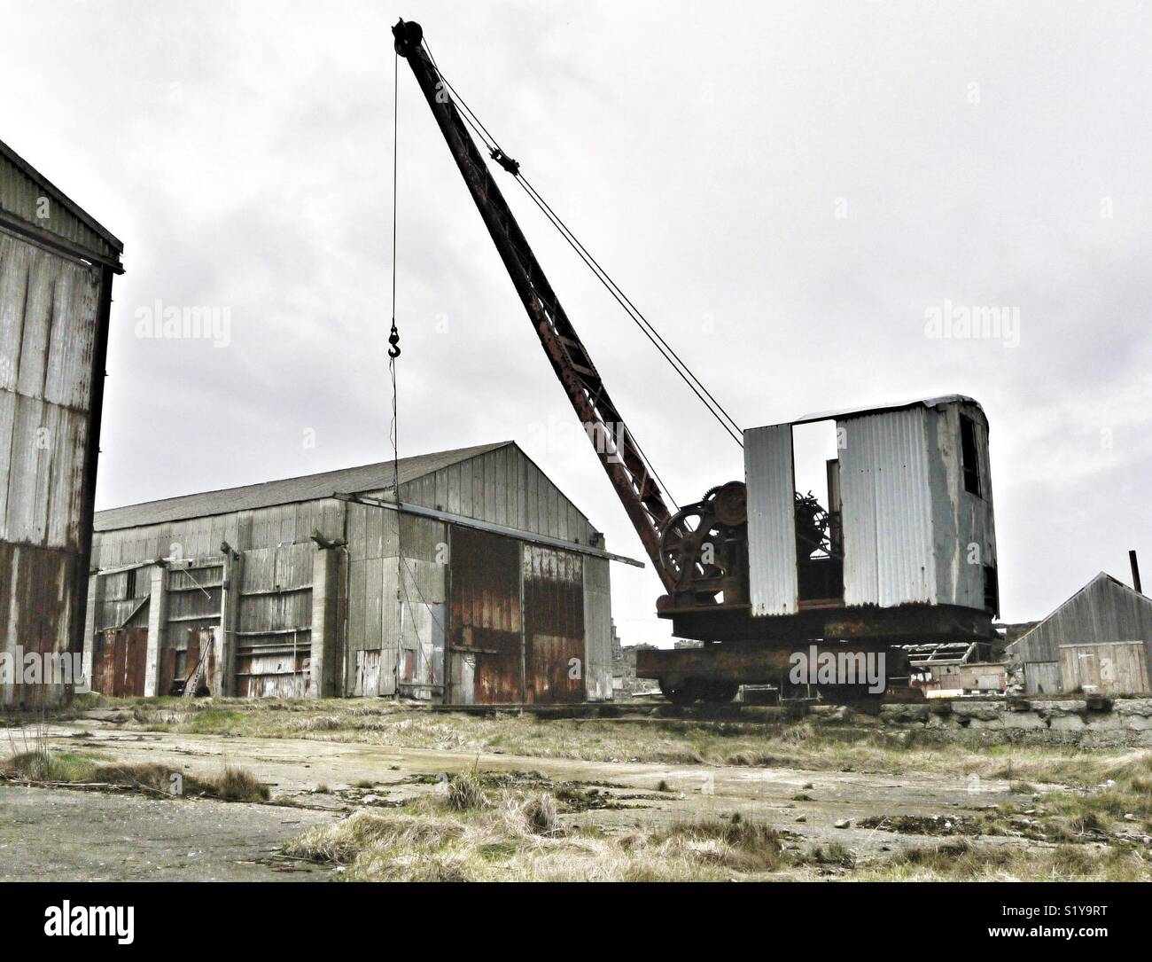 Derelict warehouses and crane in Scottish town. Stock Photo
