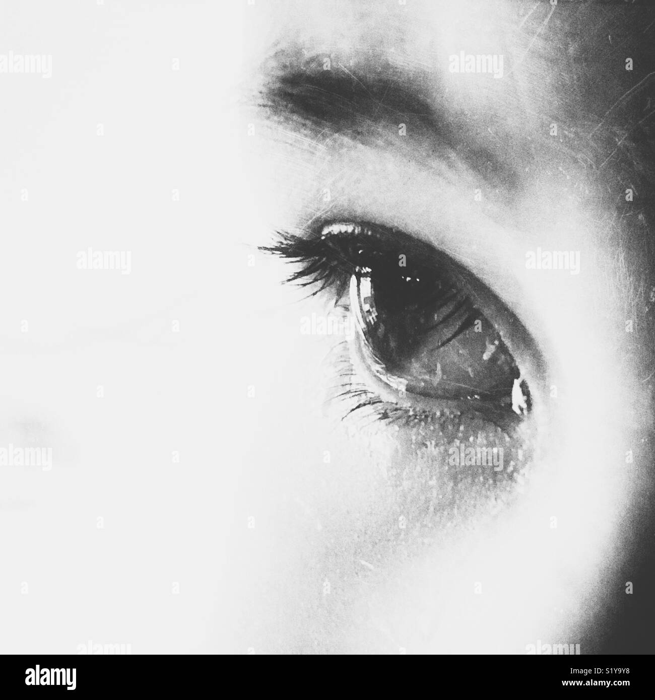 Black and white close up of teary childs eye