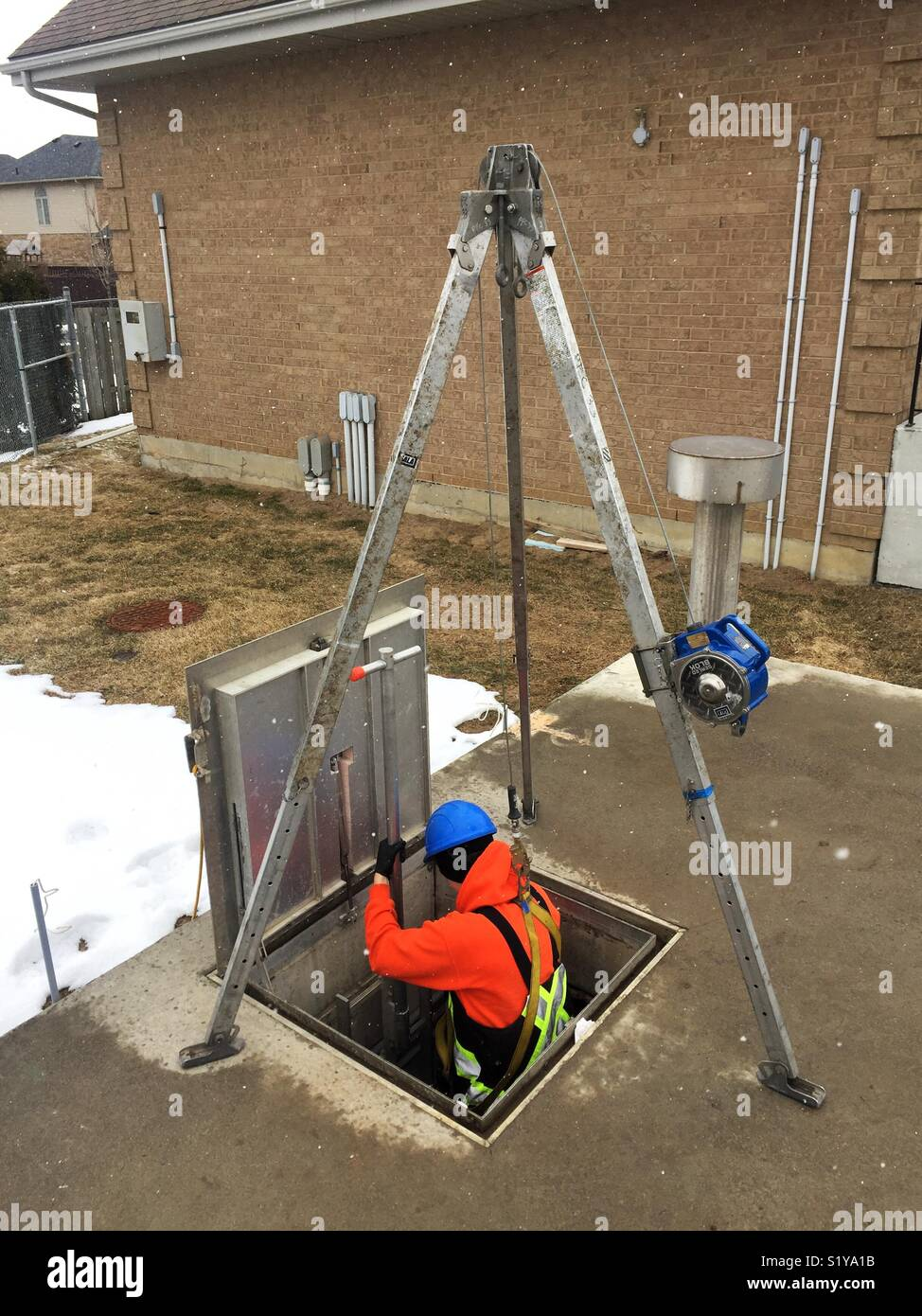Worker entering a confined space using tripod and winch - Stock Image