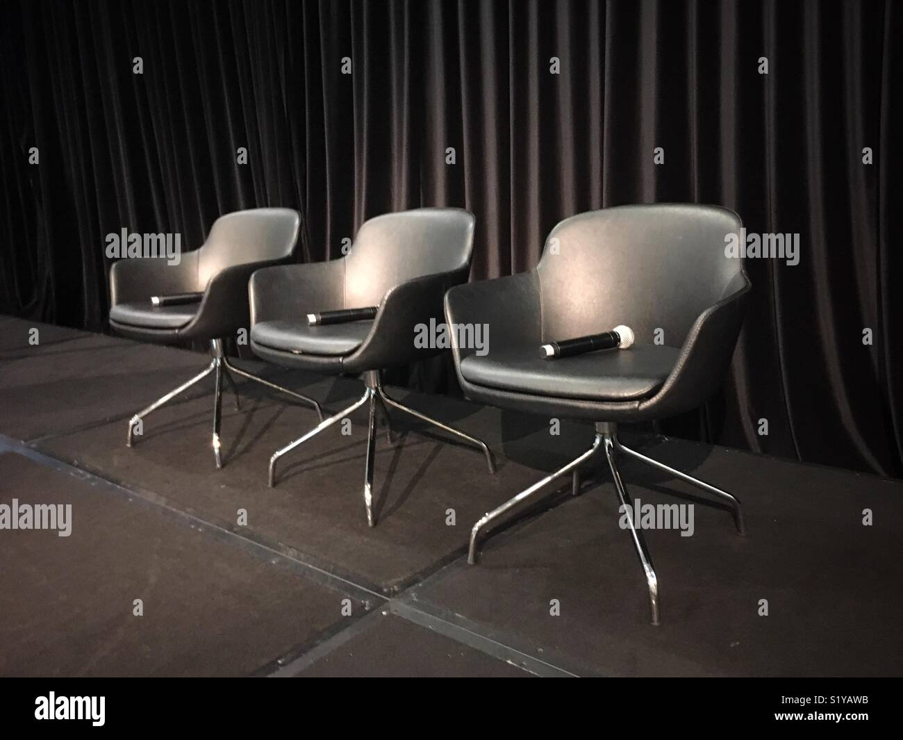 Three chairs with microphones against a black curtain. - Stock Image